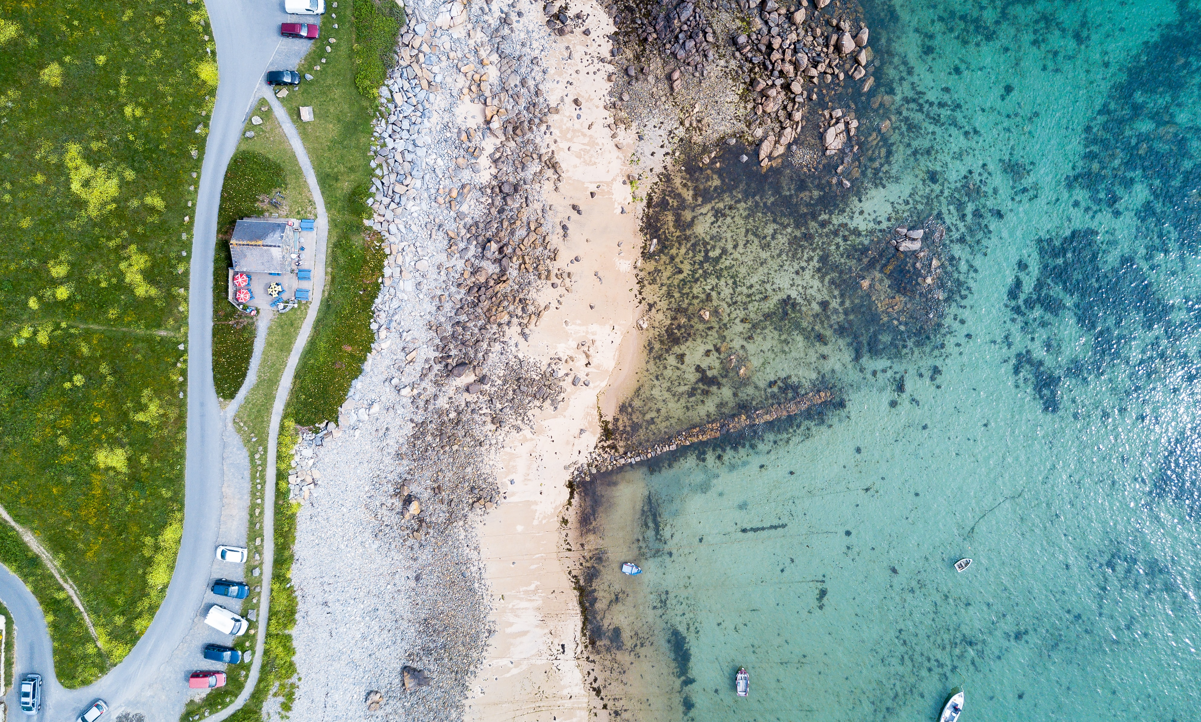 Drone view of a street by the rocky beach in La Valle, Guernsey