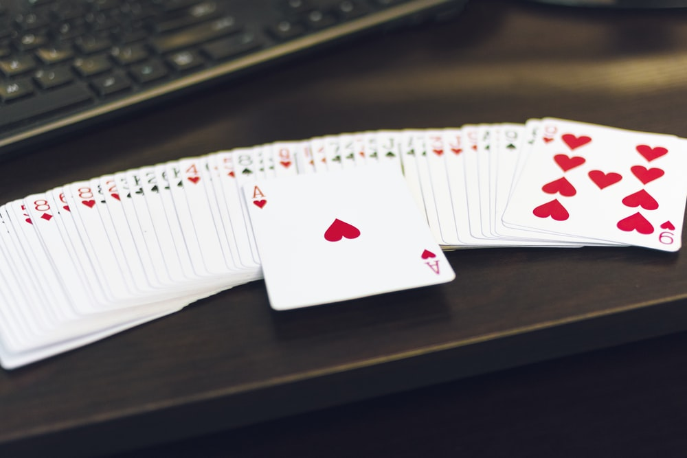 white and red playing cards on white paper