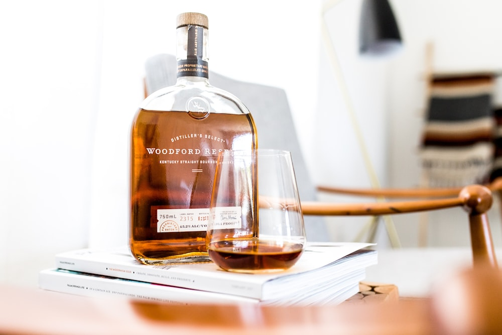Boole of Woodford Reserve whiskey atop a stack of magazines