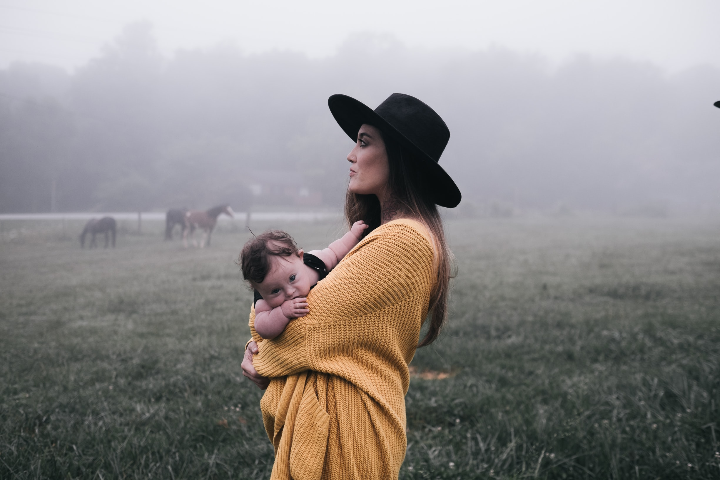 On a misty day, a woman in a big sweater and black hat holds a child in a field of horses