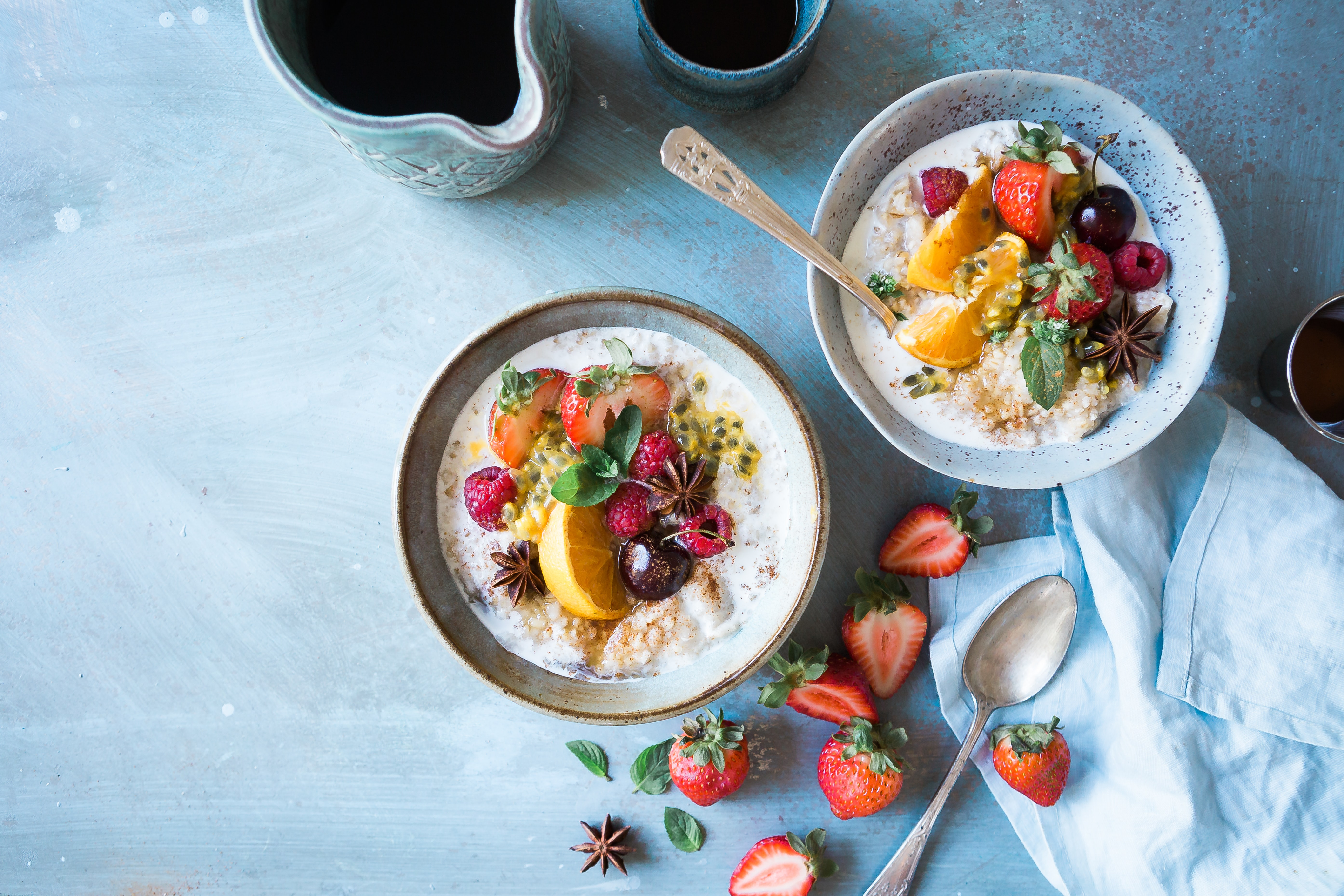 Flat lay of healthy breakfast with bowls of fruit and oatmeal