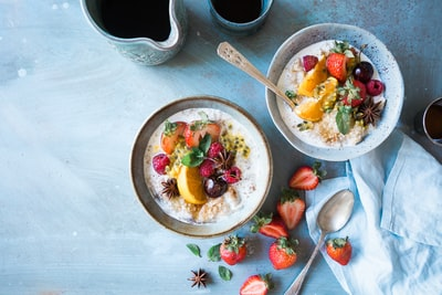 two bowls of oatmeal with fruits breakfast zoom background