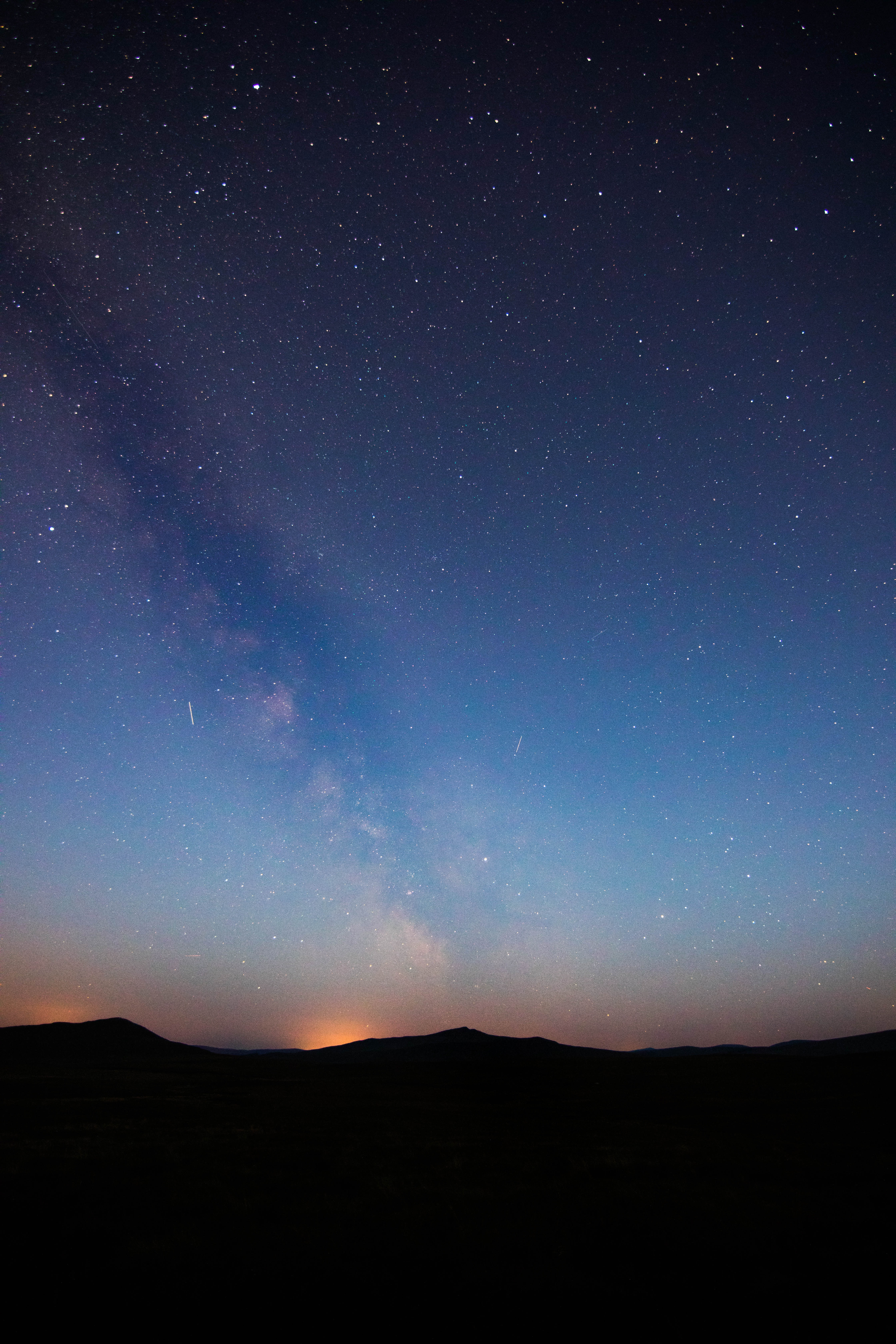 Bright stars in the beautiful dark blue night sky over a silhouette of a mountain range