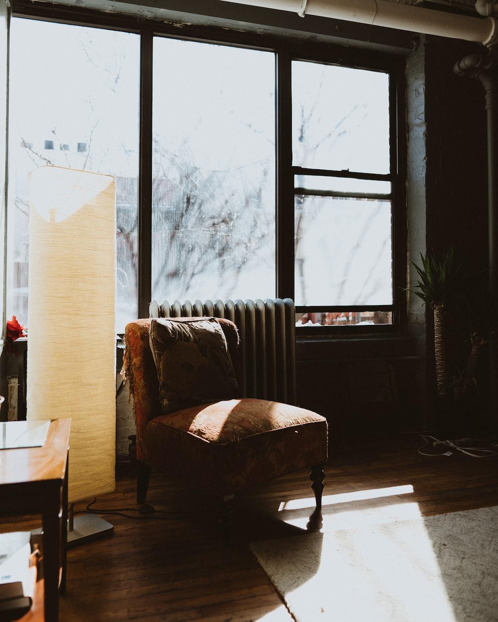 brown fabric chair near beige floor lamp
