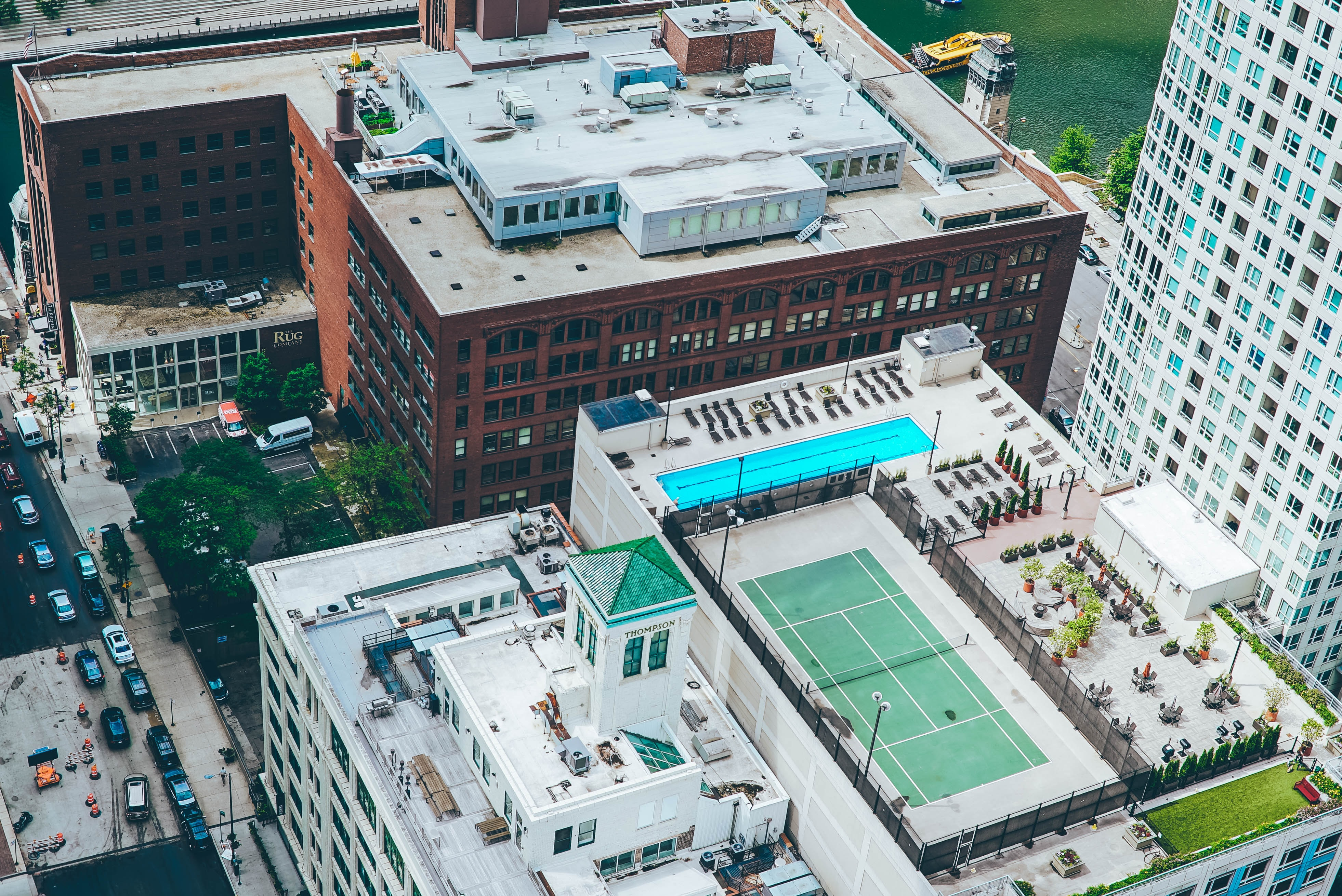 aerial view photo of tennis court and swimming pool on top of building along the road