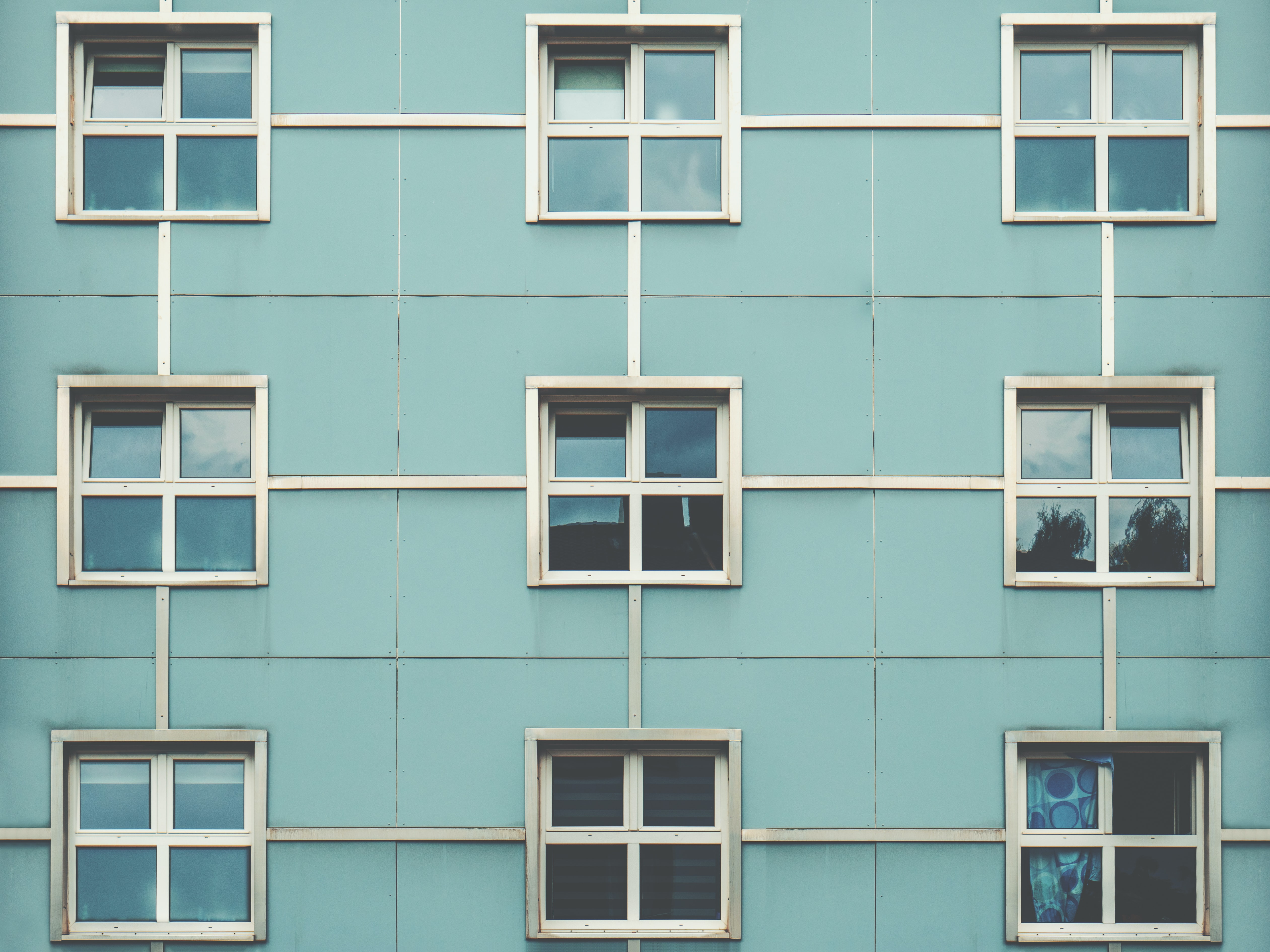 Symmetrical square windows in the blue wall of a building in Cologne.