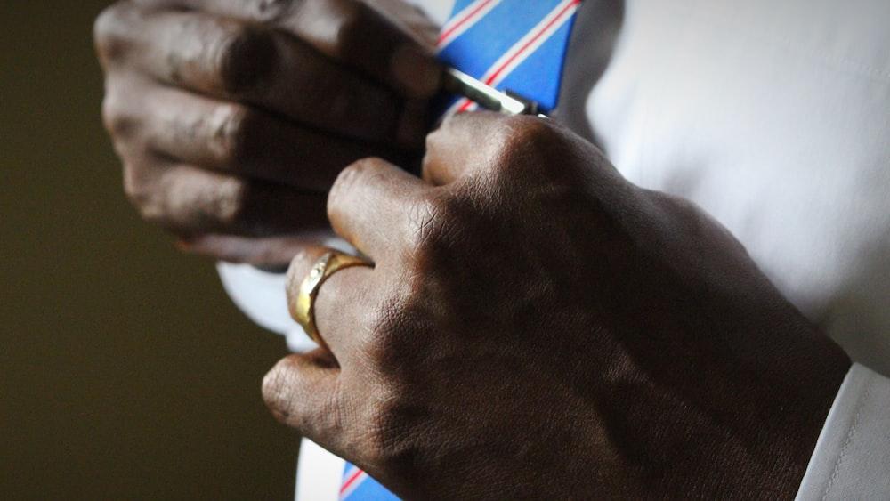 person holding blue necktie
