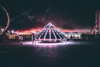 person standing near triangular carnival ride edc teams background