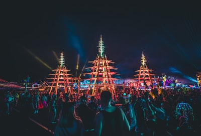 people gathering in front of brown tower during nighttime edc teams background