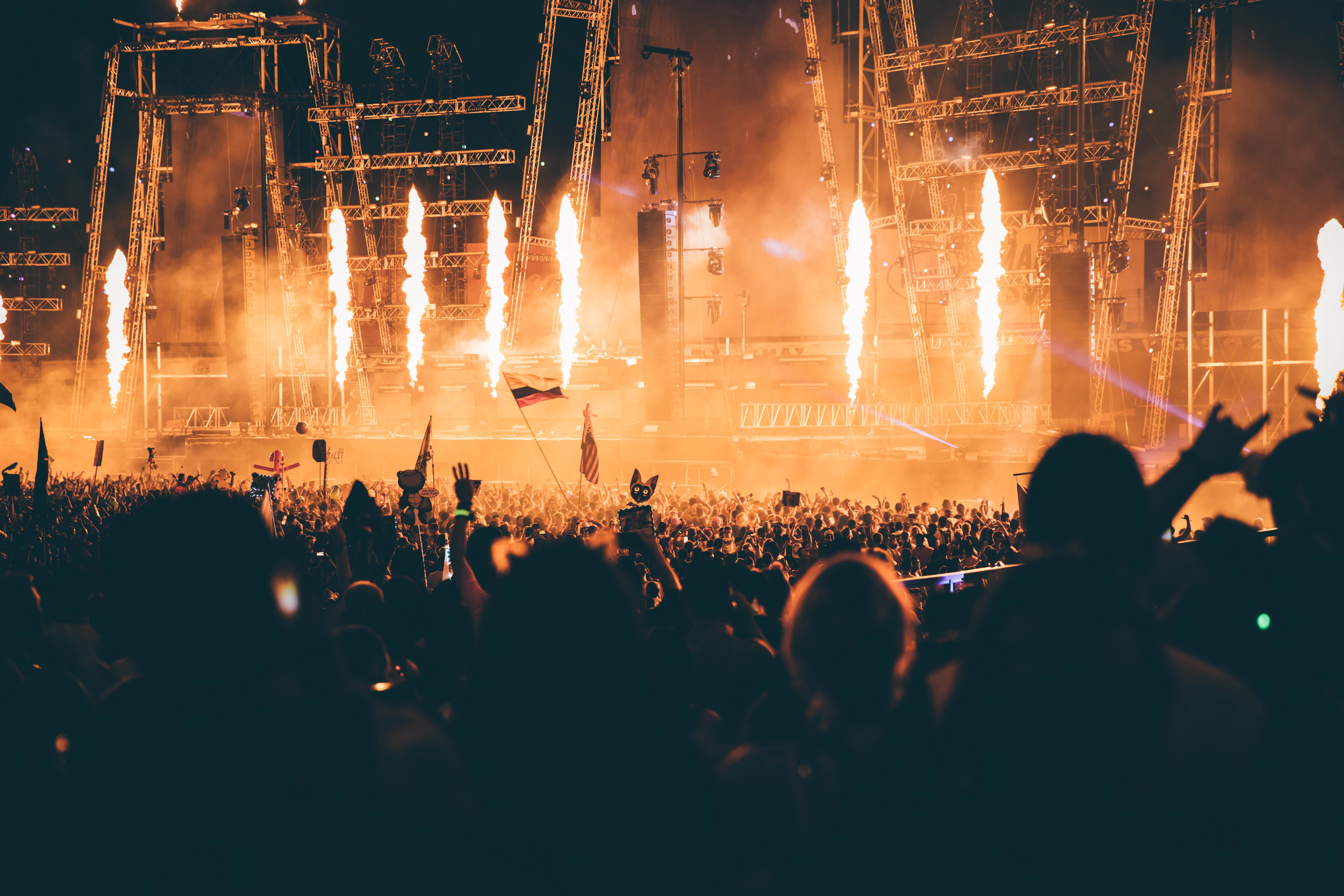 A crowd of people enjoying a concert with columns of flame on the stage in Las Vegas