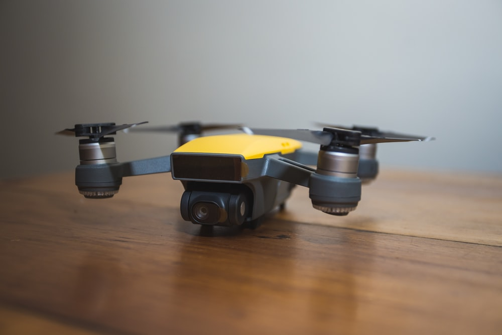 yellow and black DJI drone on wooden surface