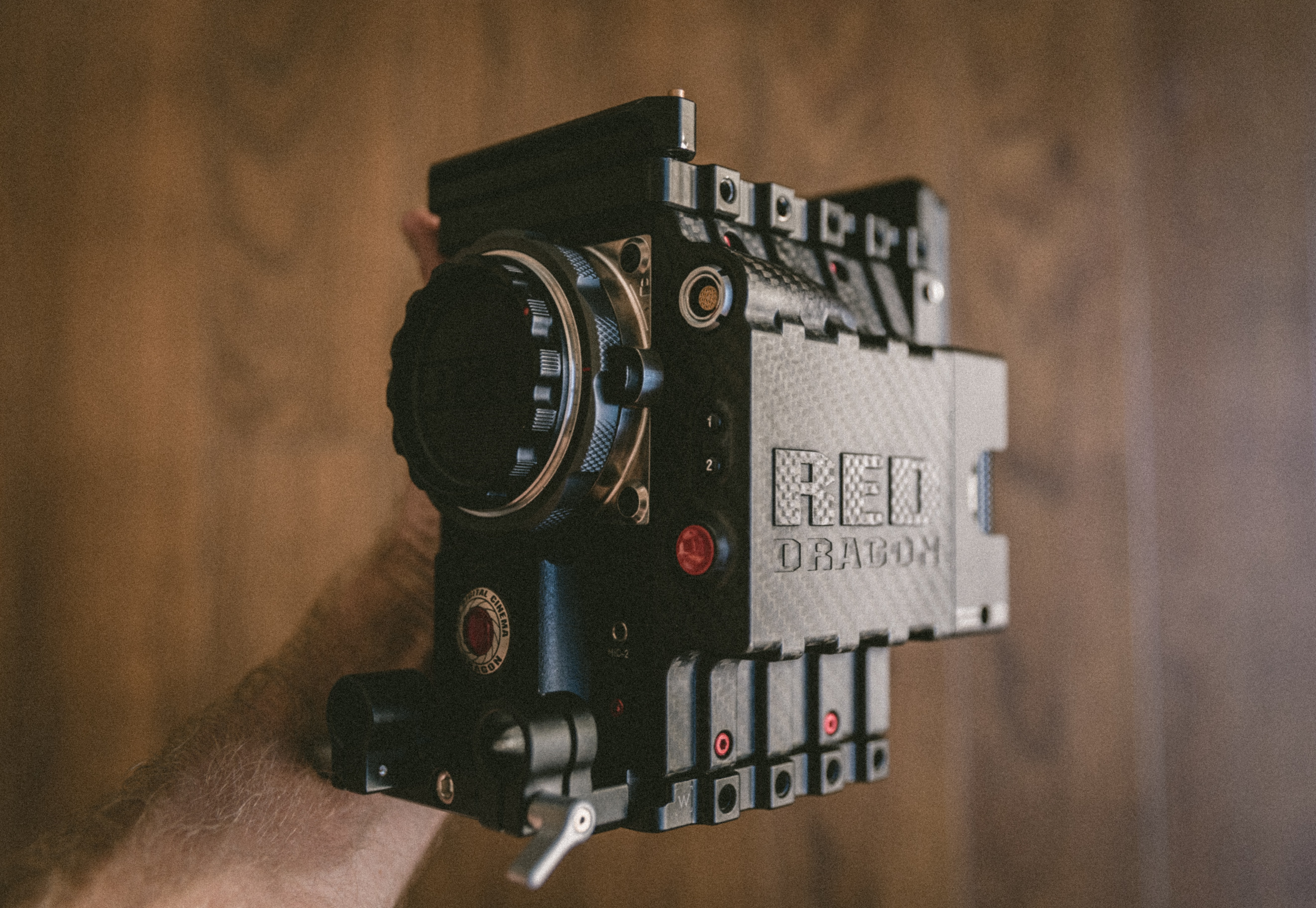 A person's hand holding a professional RED Dragon video camera