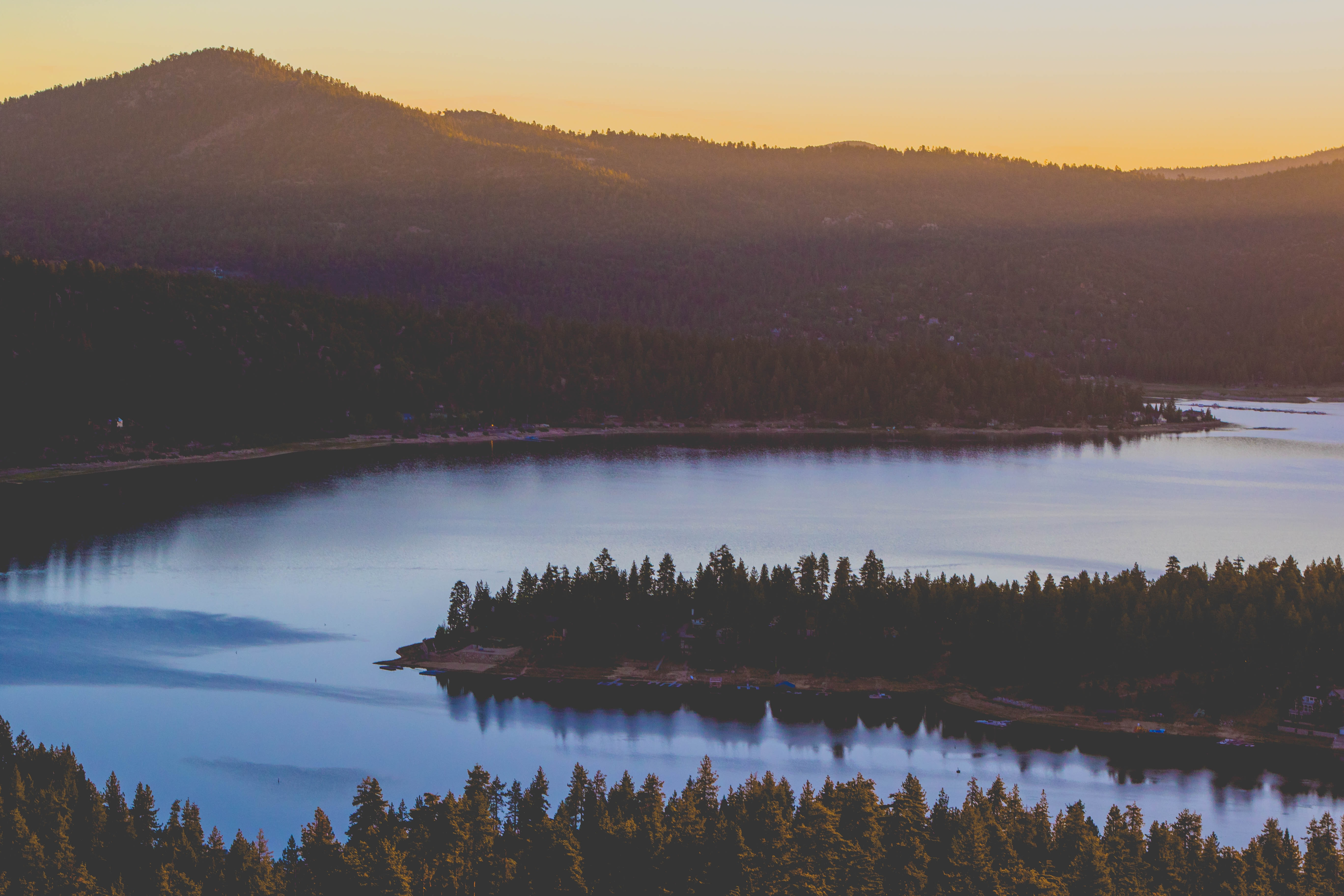 A view of the lake and tree covered land and hillsides at Big Bear Lake during the golden hour