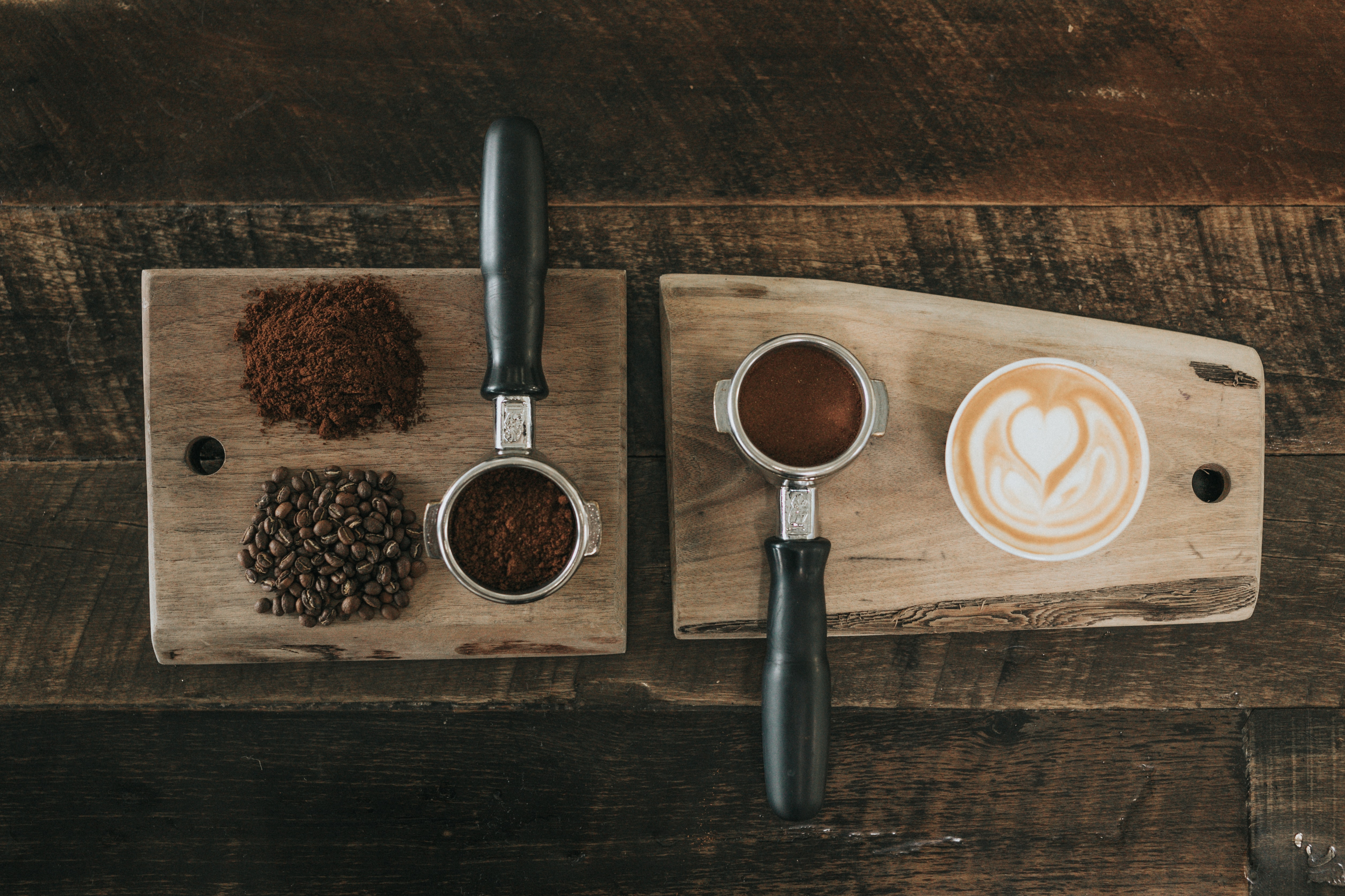 An overhead shot of two coffee machine portafilters next to coffee beans and a cup of coffee