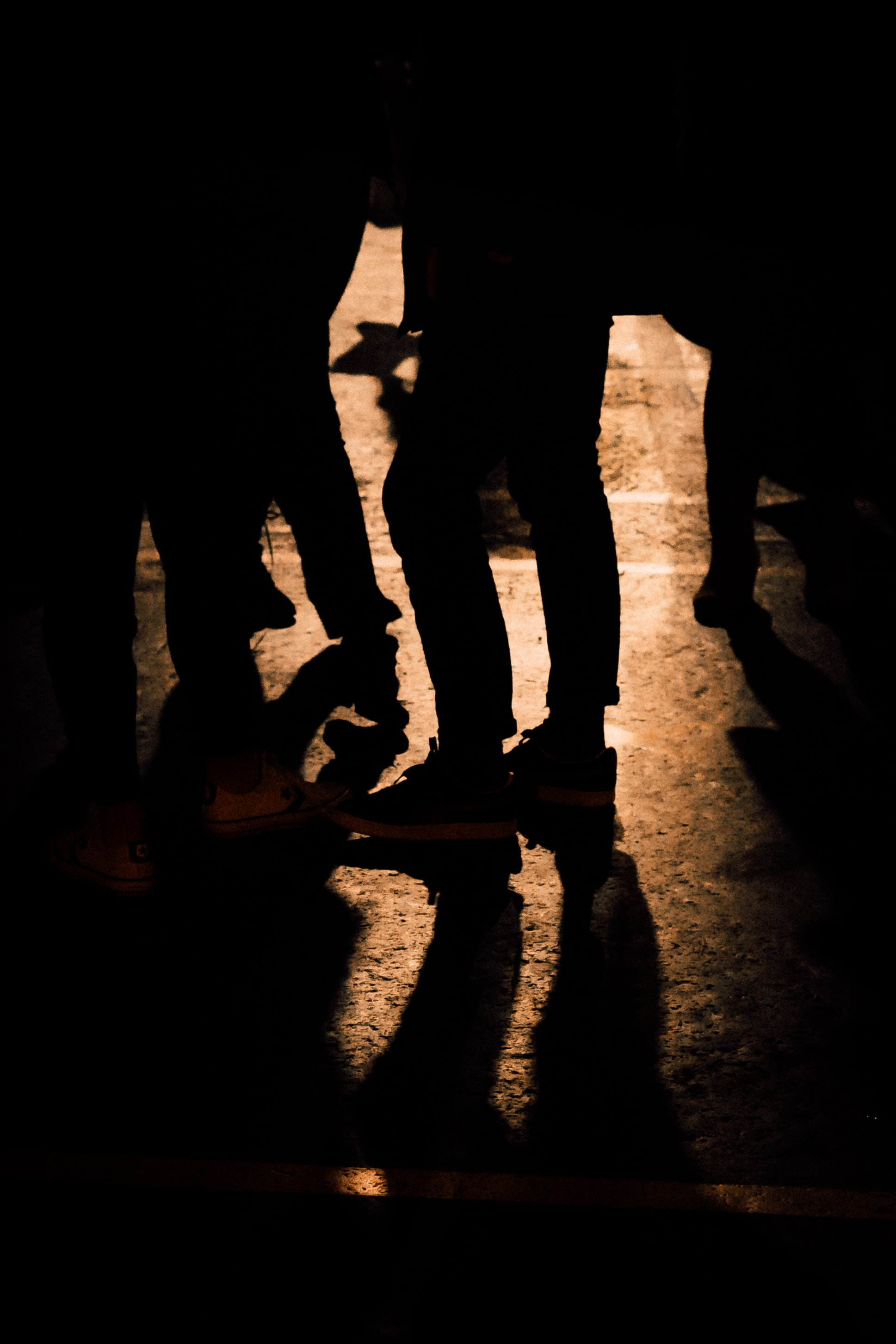 Silhouettes of people standing in a dimly-lit street seen from the waist down