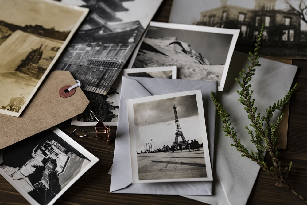 grayscale photo of Eiffel tower on top of white envelope