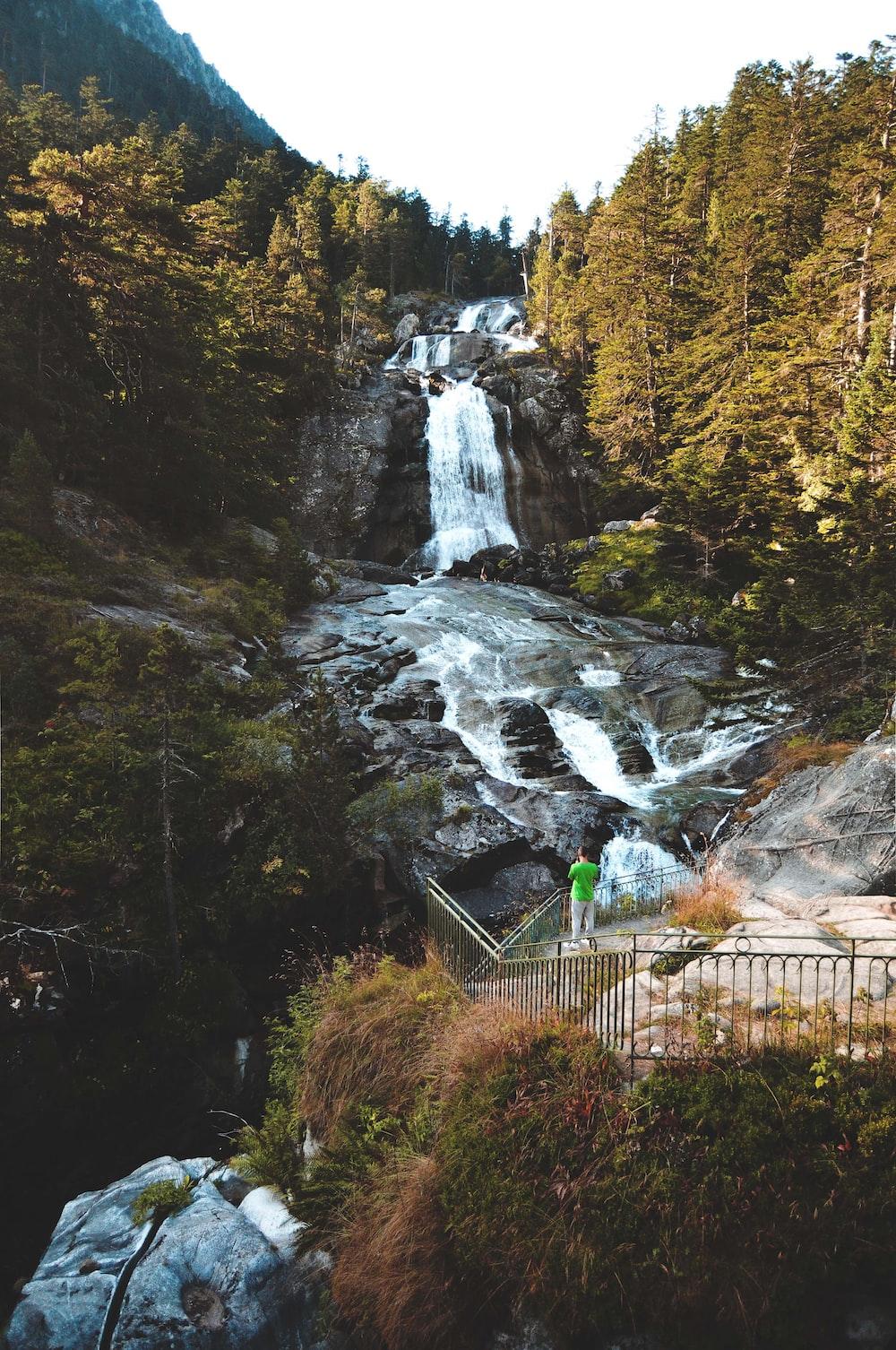 green metal fence near waterfalls during daytime