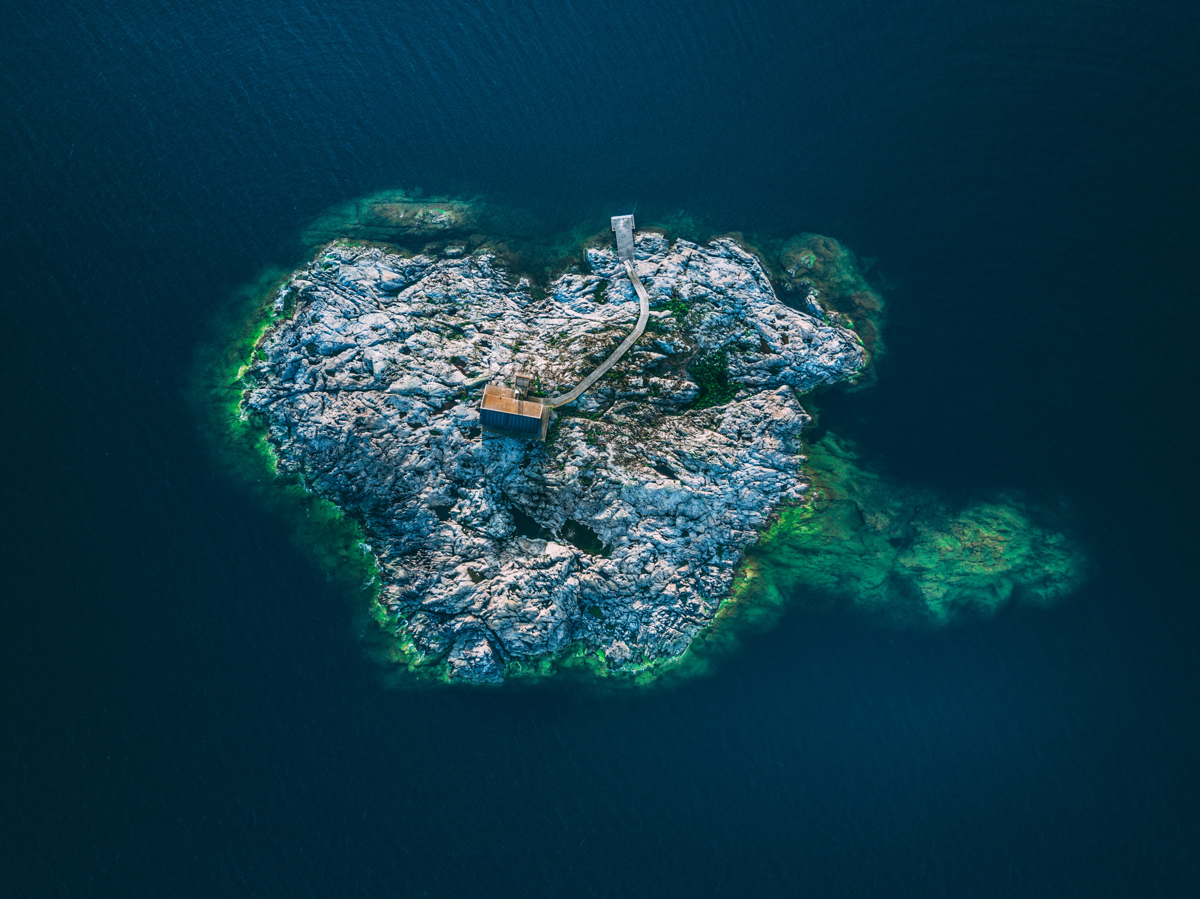 A drone shot of a small building in the middle of a rocky island