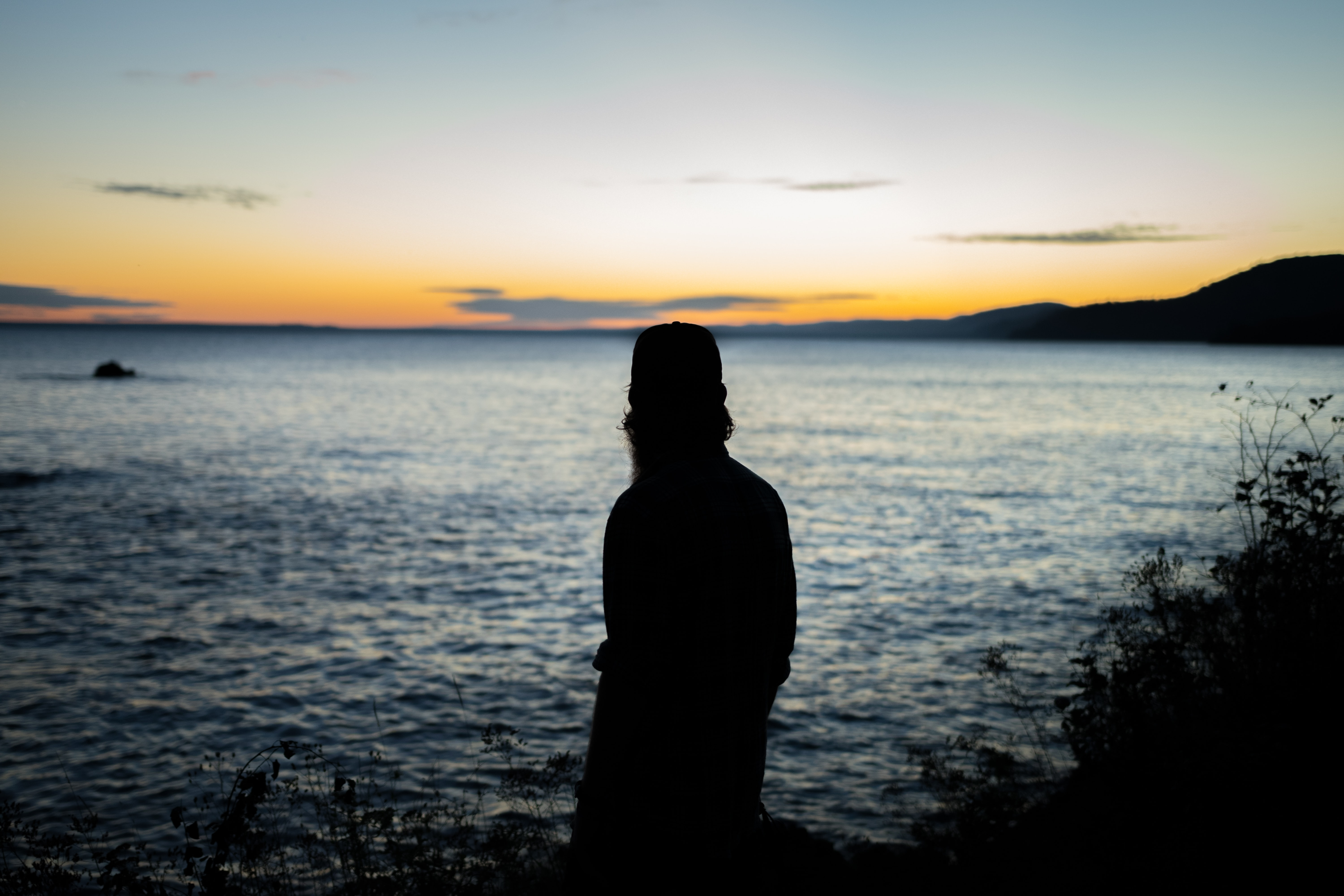 silhouette of person standing near water
