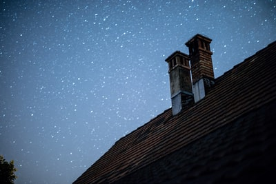 brown and black wooden house under starry night chimney teams background