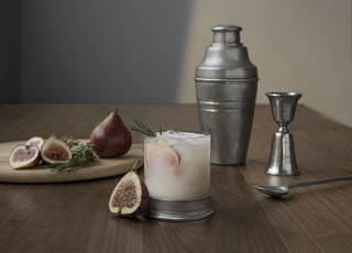 sliced oval brown fruit beside glass cup