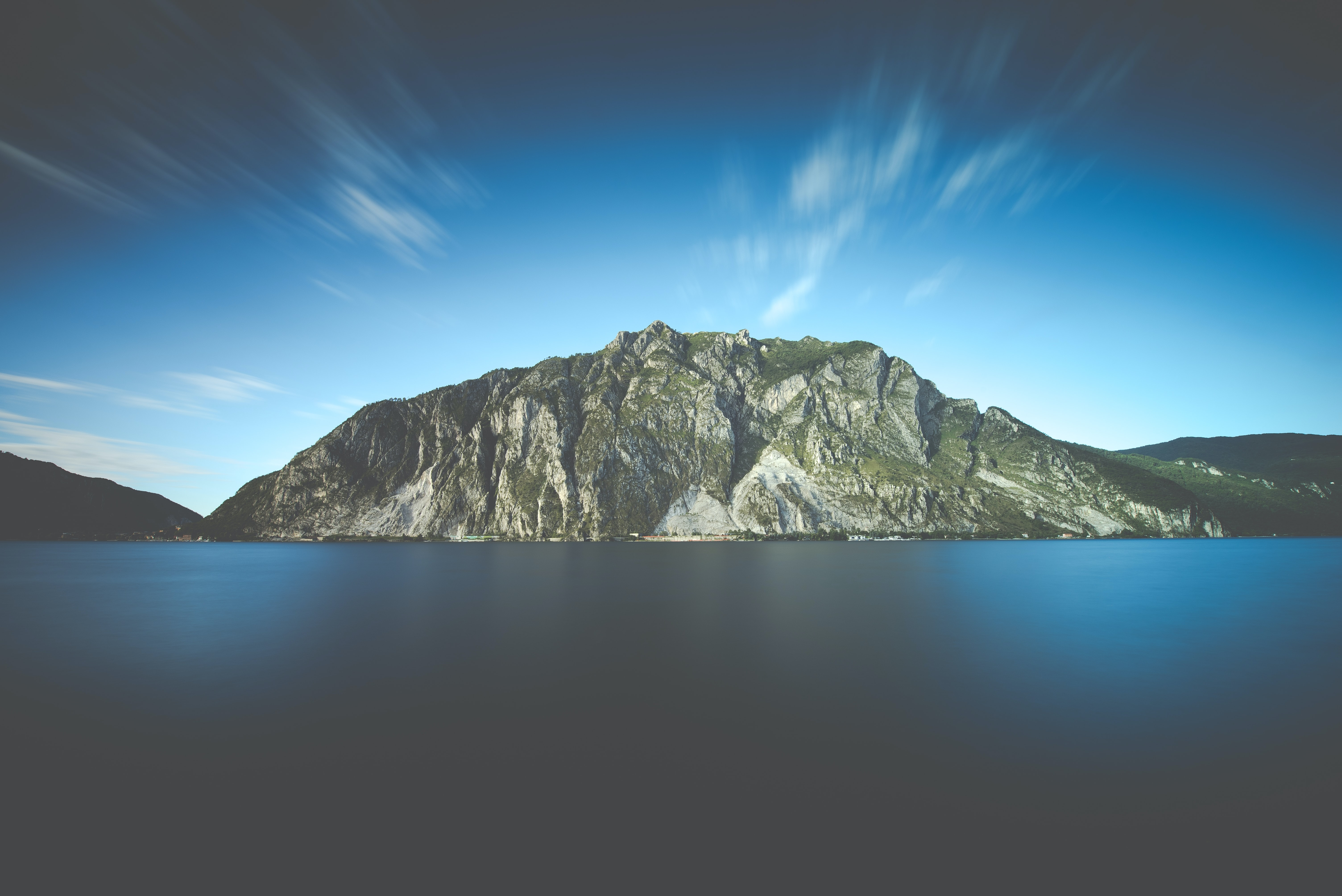 A rock mountain surrounding a body of water with moving clouds up in the sky