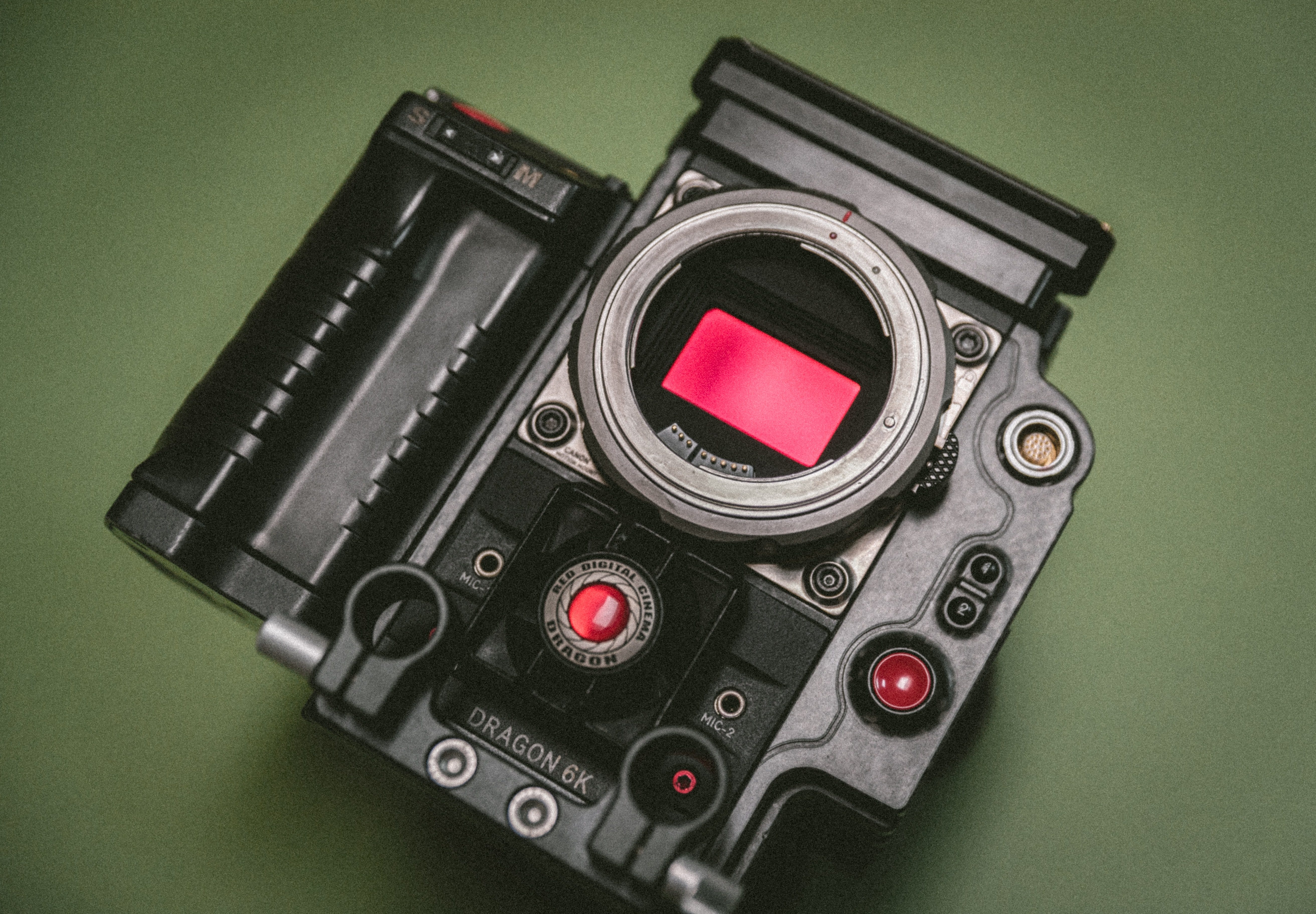 Black Dragon camera with red screen and buttons sits on green surface