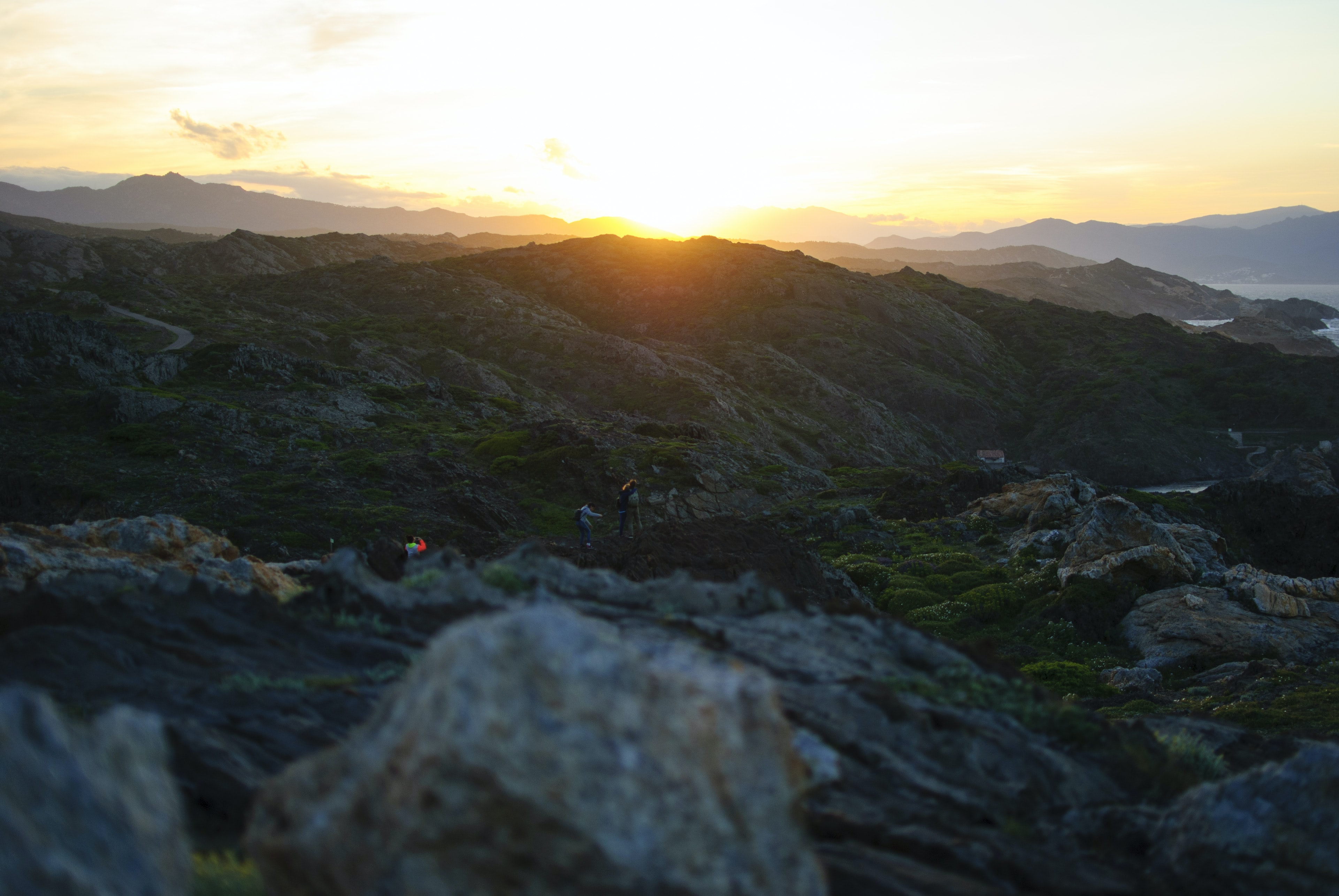 A small group of hikers walking rocky terrain as sun sets over distant hills