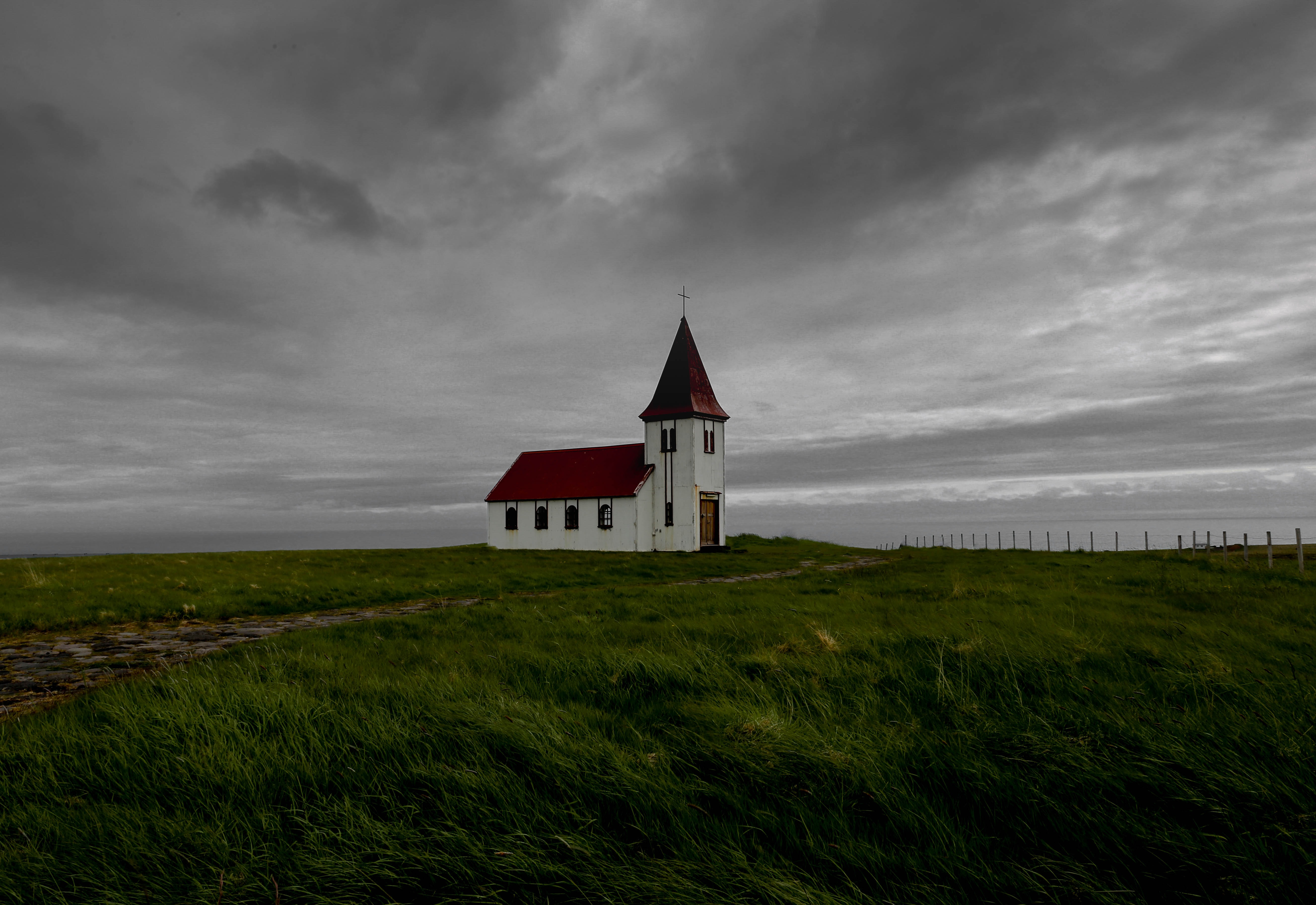 A white church building in the middle of farmland near the ocean, covered by gray clouds.
