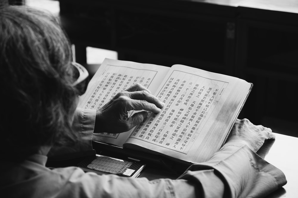 grayscale photography of person reading book