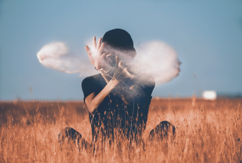 man sitting on brown grass field playing with smoke
