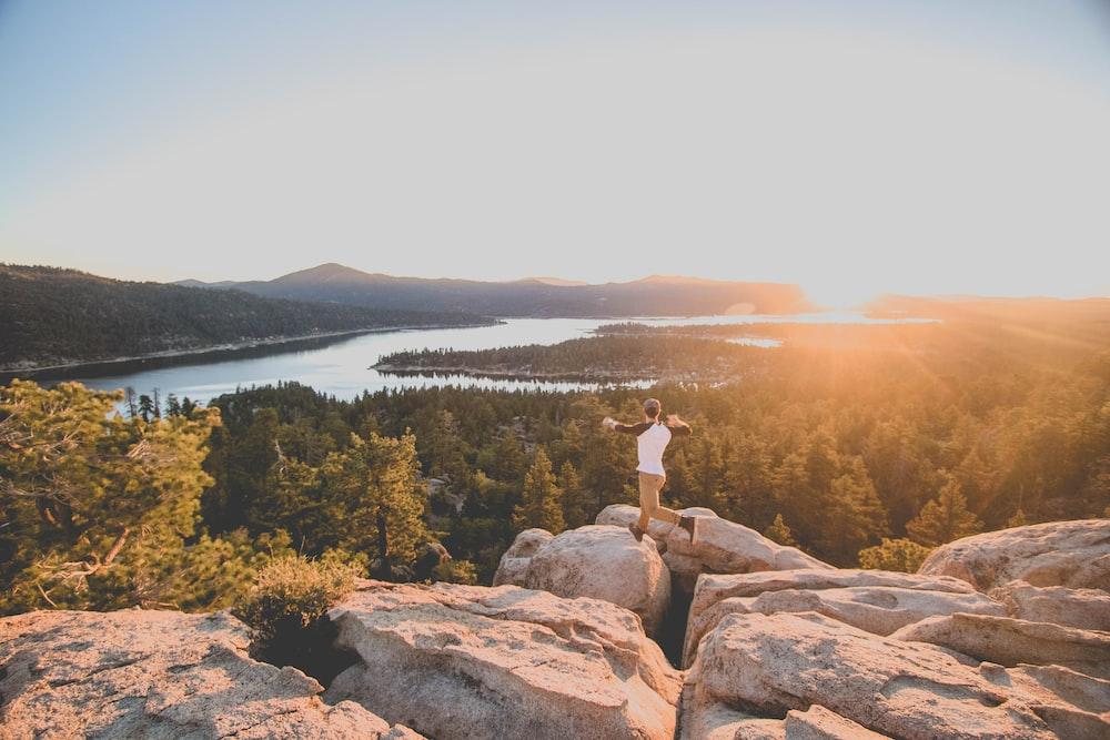 man jumping on rocky mountain golden golden hour