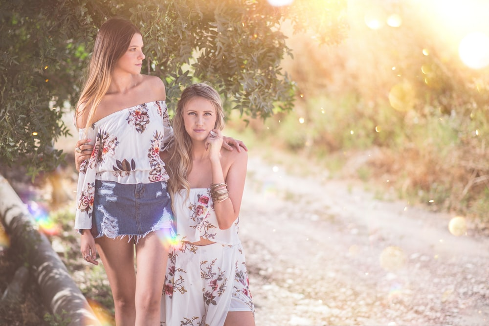 two women standing beside tree