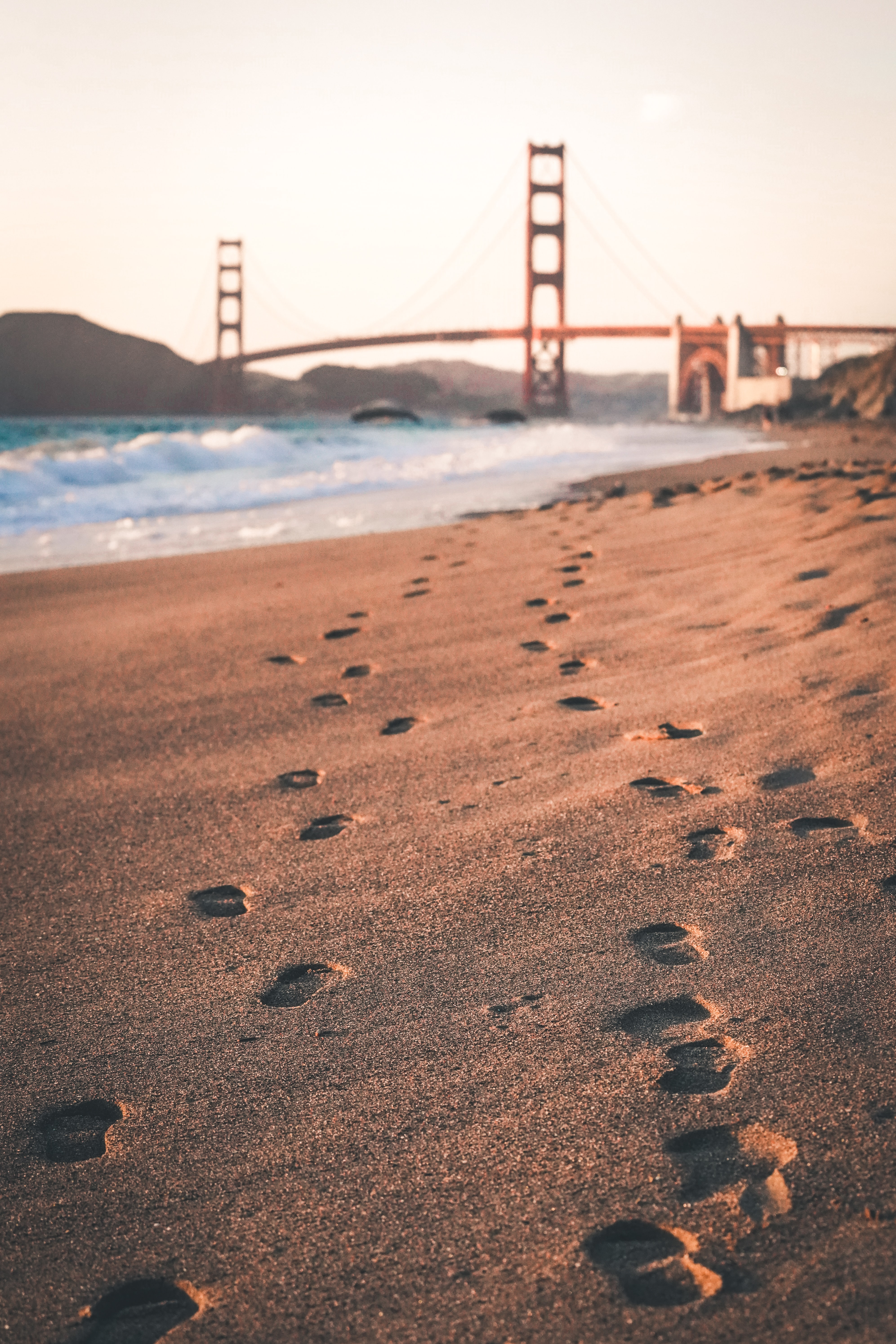 Footprints in the sand with the Golden Gate bridge in the background in San Francisco