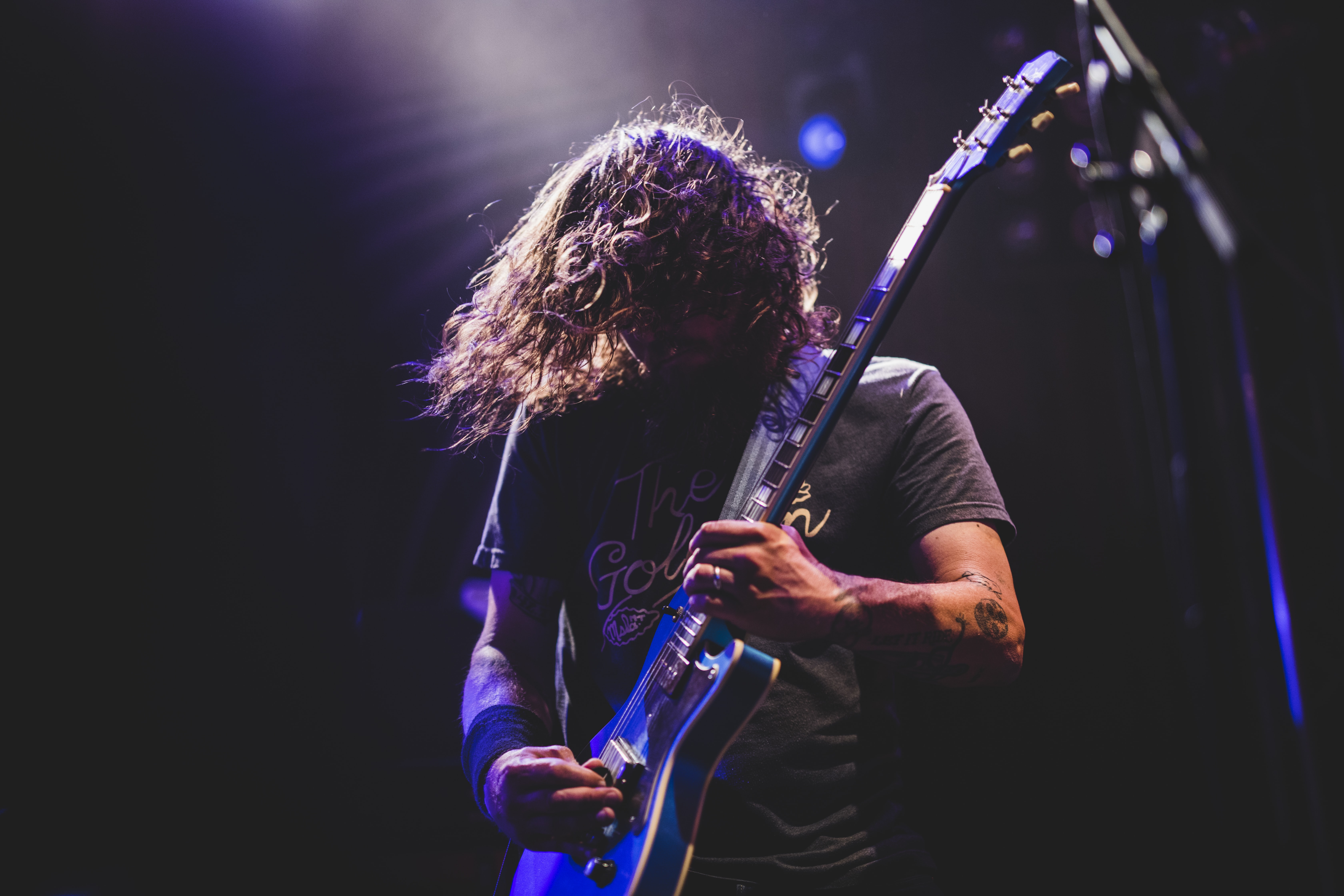 A long-haired man in a t-shirt  playing an electric guitar on stage