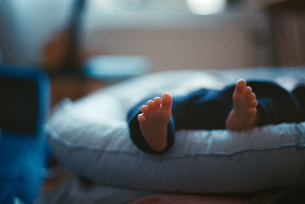 closeup photography of baby laying on bed