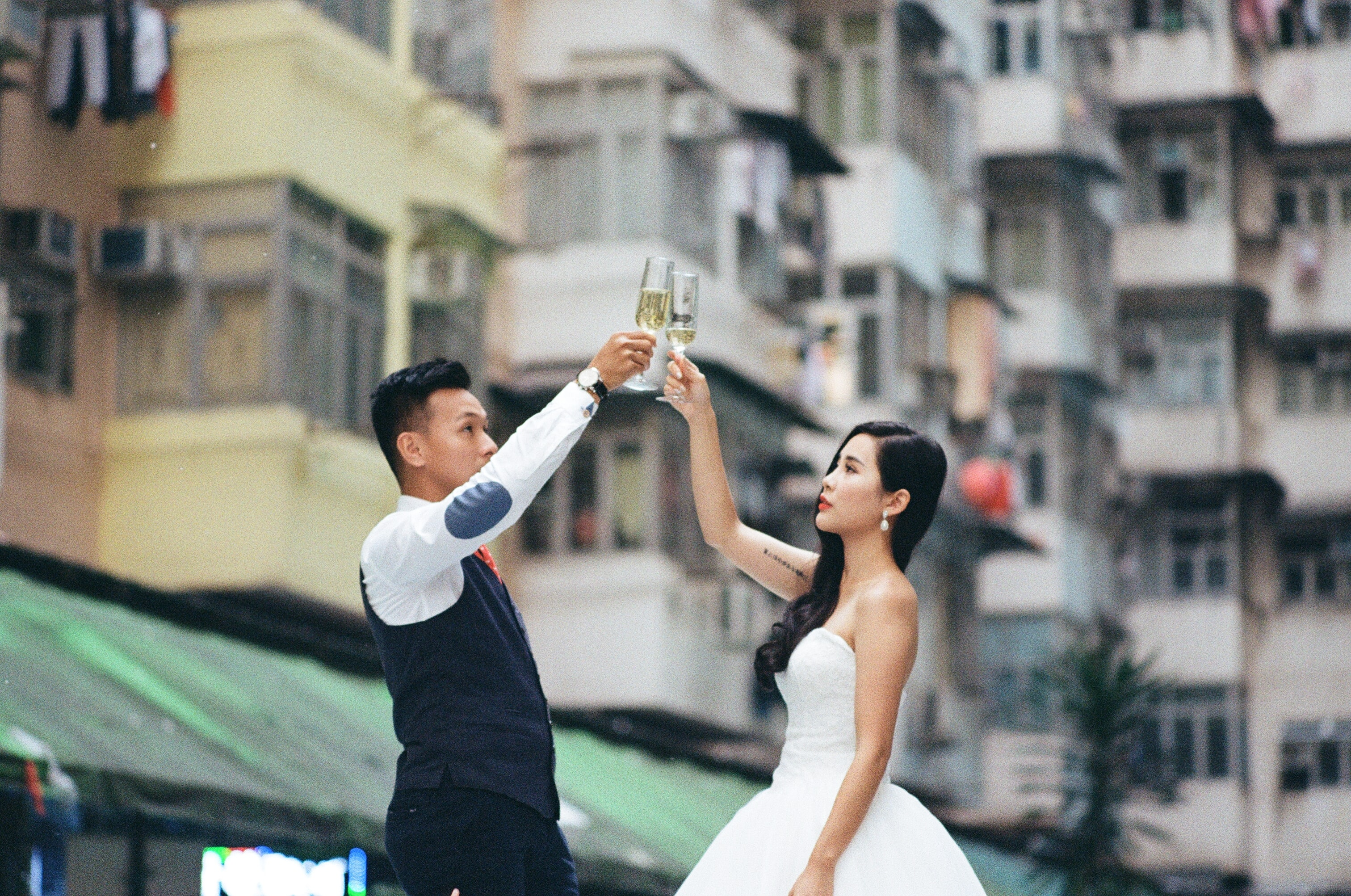 Just-married couple toasts against a city backdrop of high rises