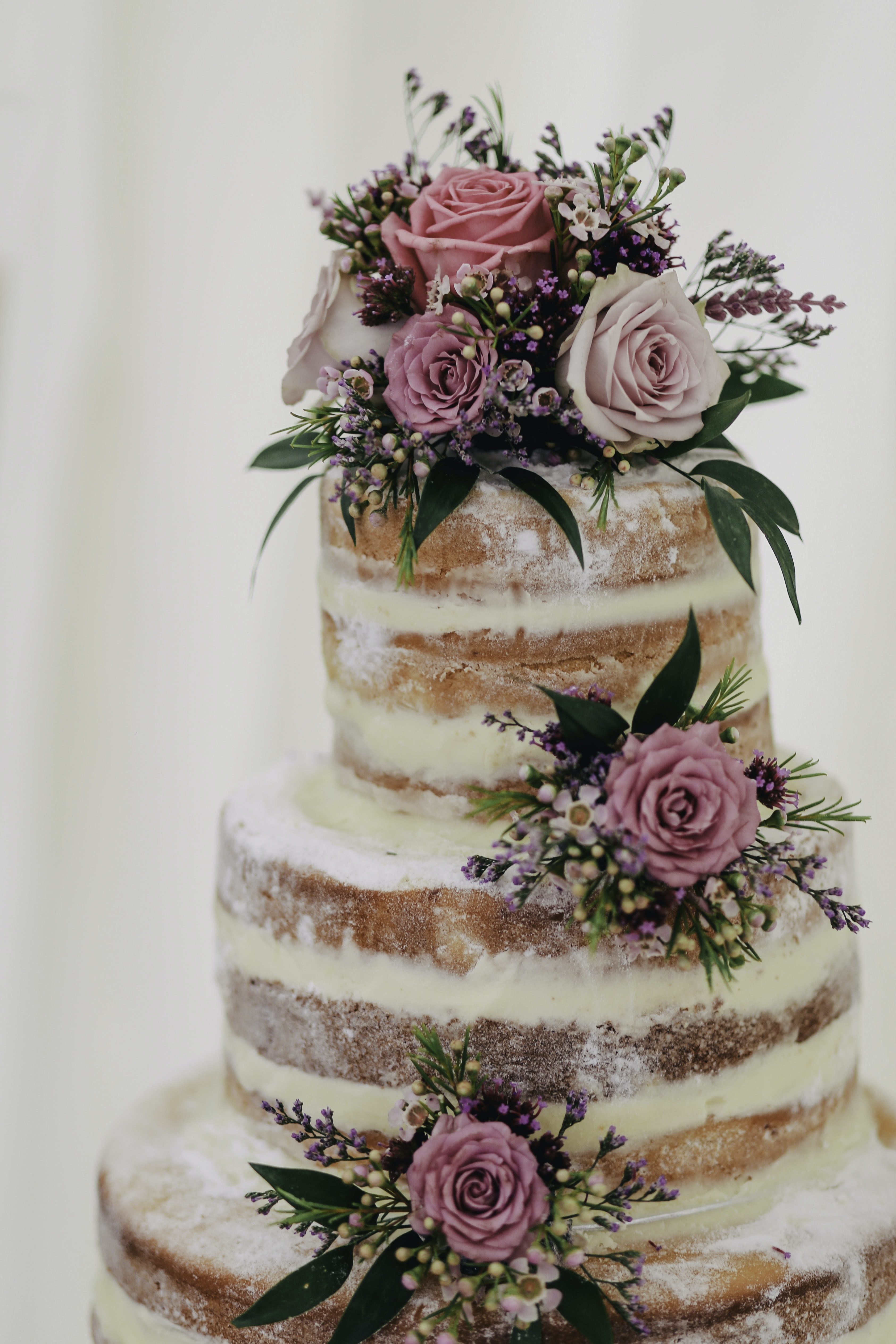 Three level wedding cake with powdered sugar and pink roses