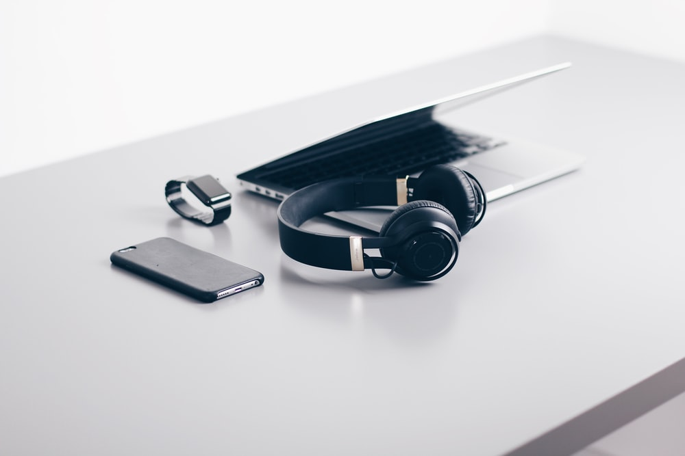 A MacBook, an iPhone, an Apple Watch and headphones on a white desk