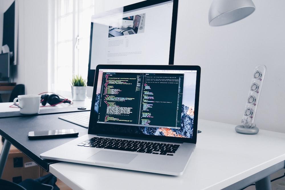 忙しい机の画面にコード行が表示されたMacBook
