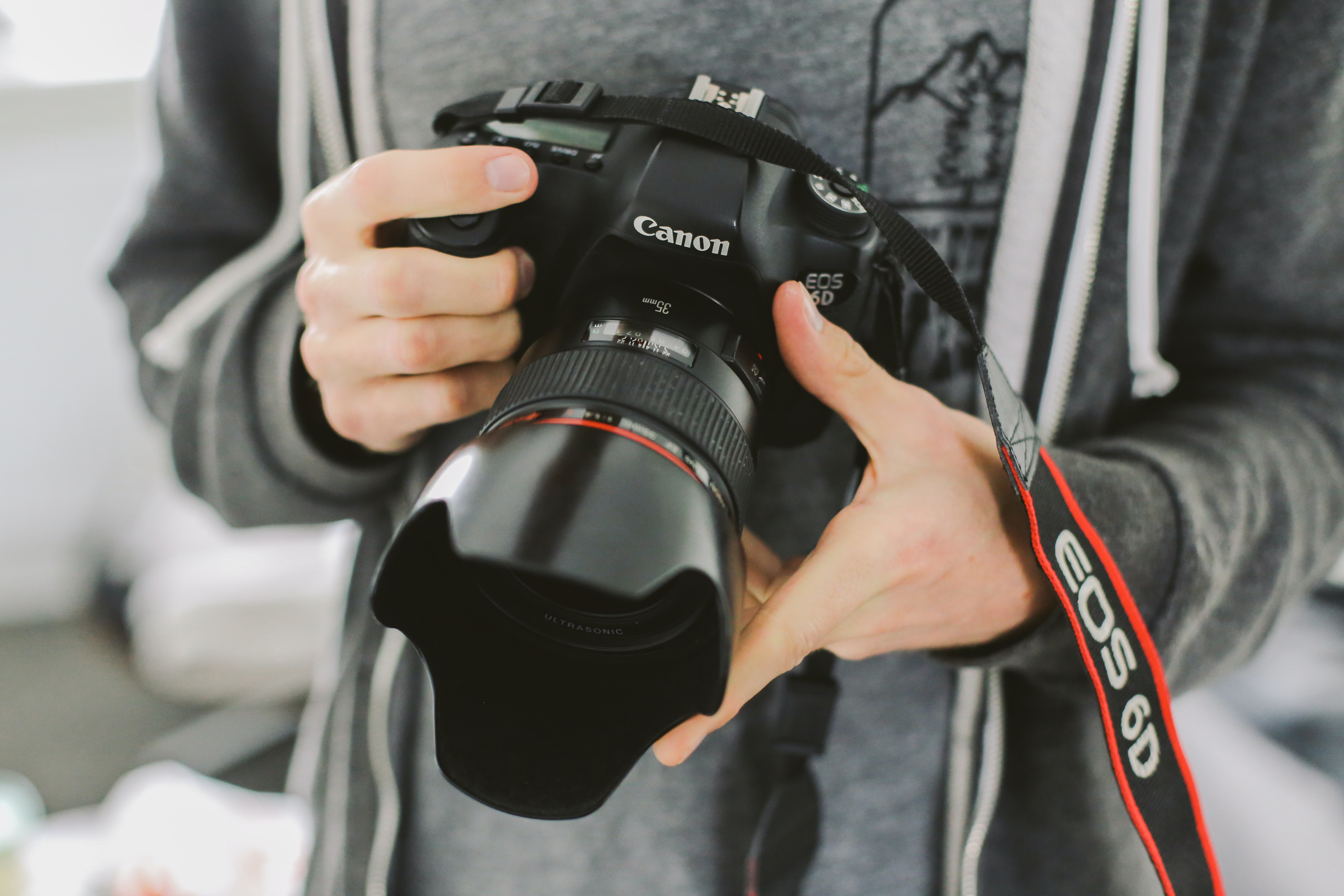 A close-up of a photographer in gray sweater holding a Canon EOS 6D camera.