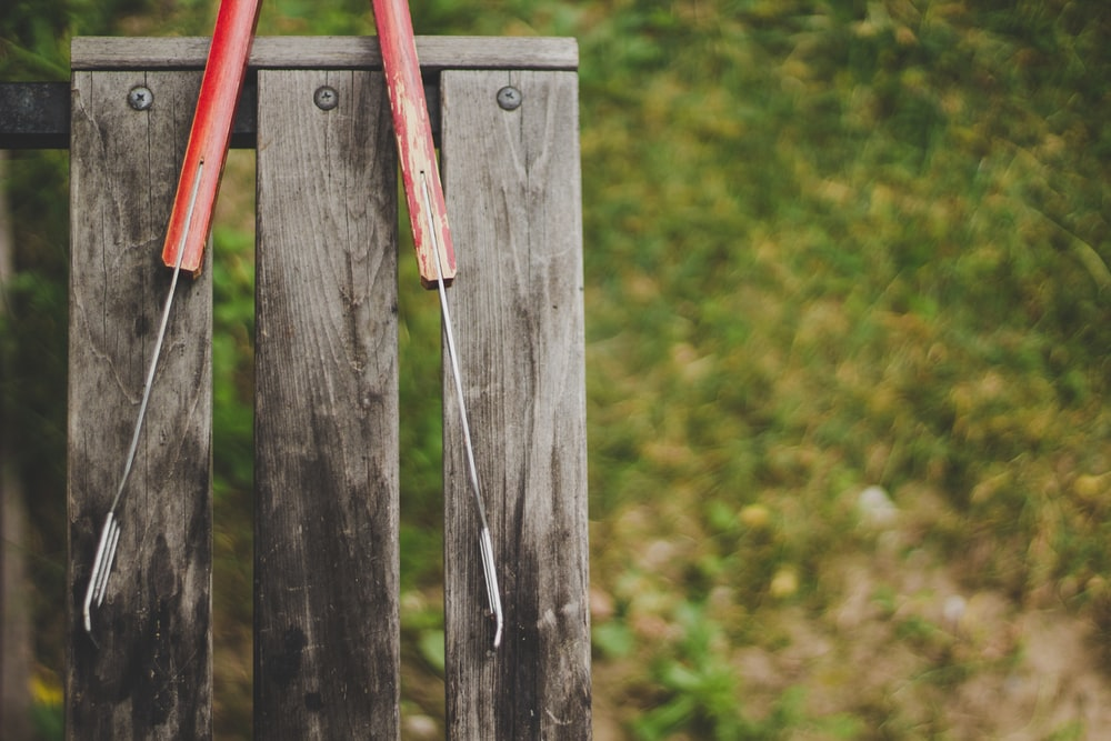 gray and red tong on wooden bench
