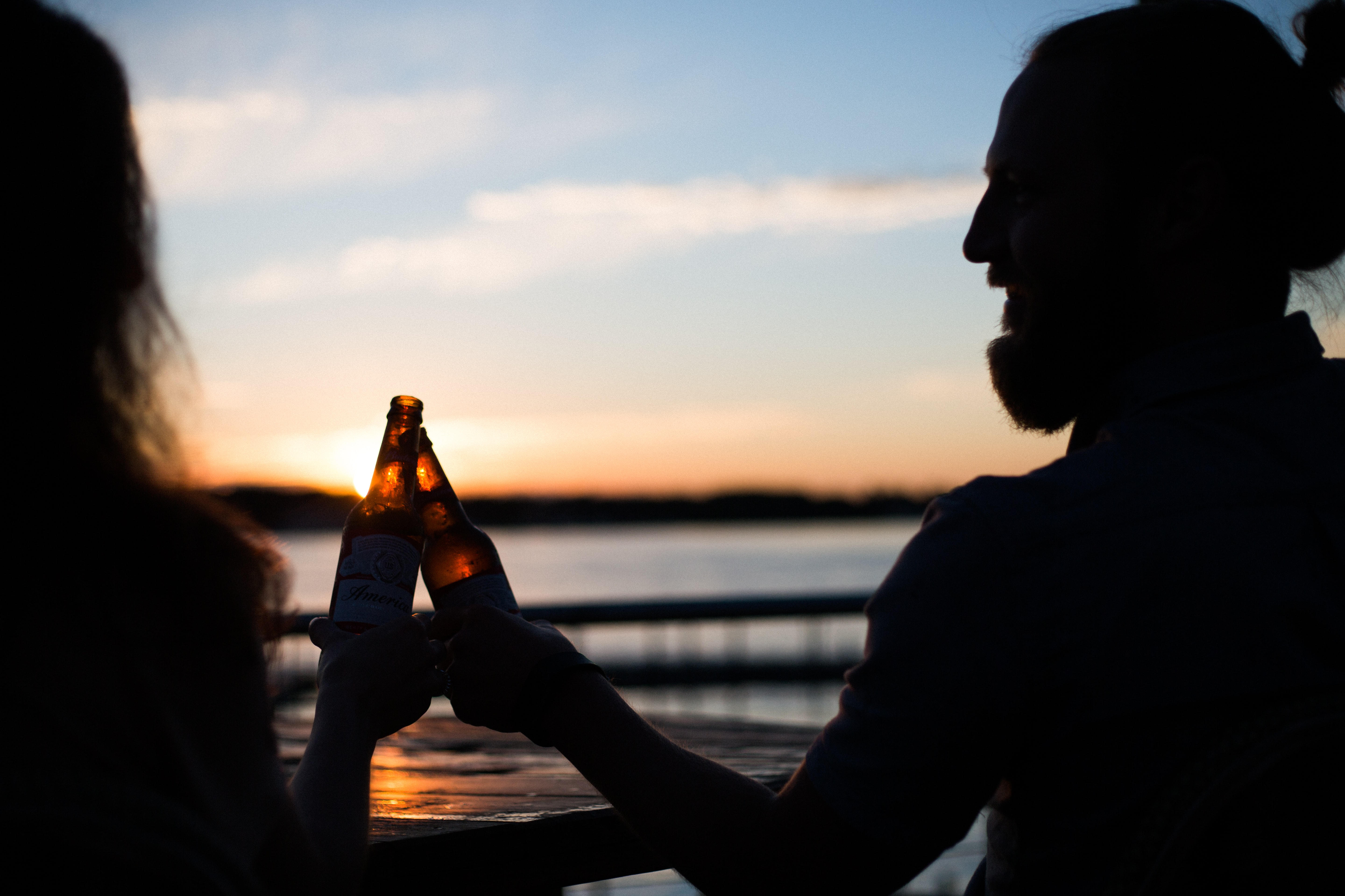 silhouette photography of man and woman carrying beer bottles