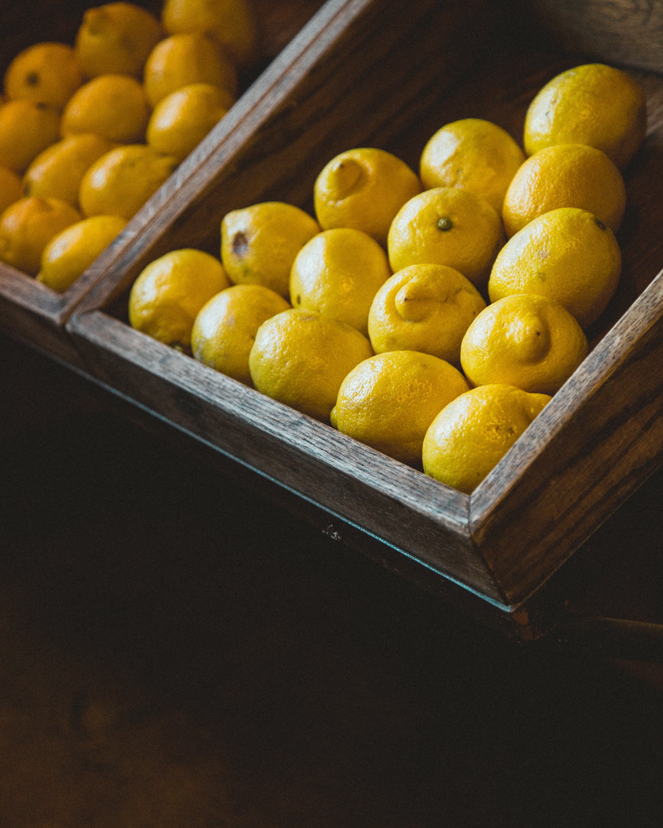 bunch of lemons on wooden rack