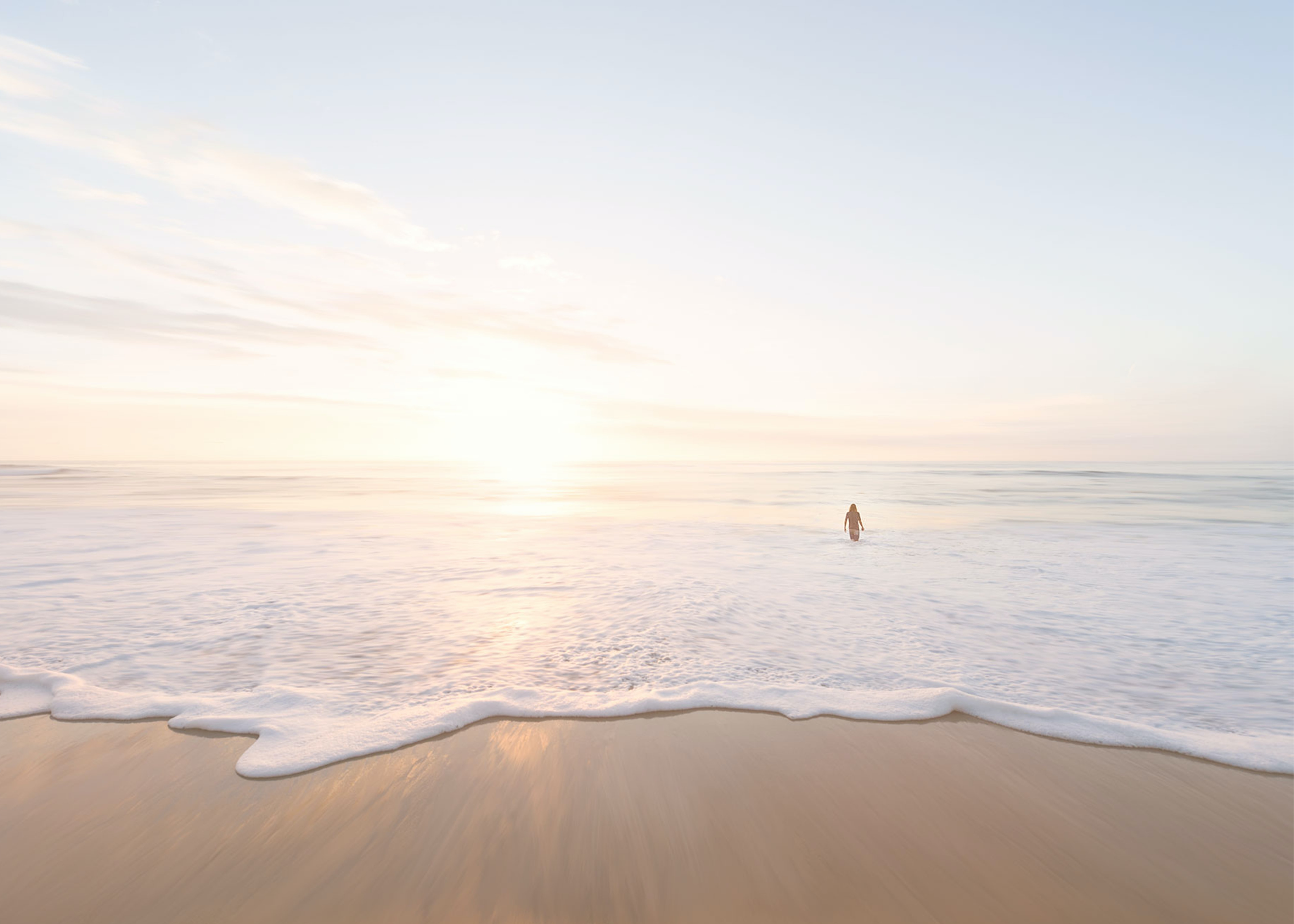 Person entering the calm ocean at the sand beach in San Diego