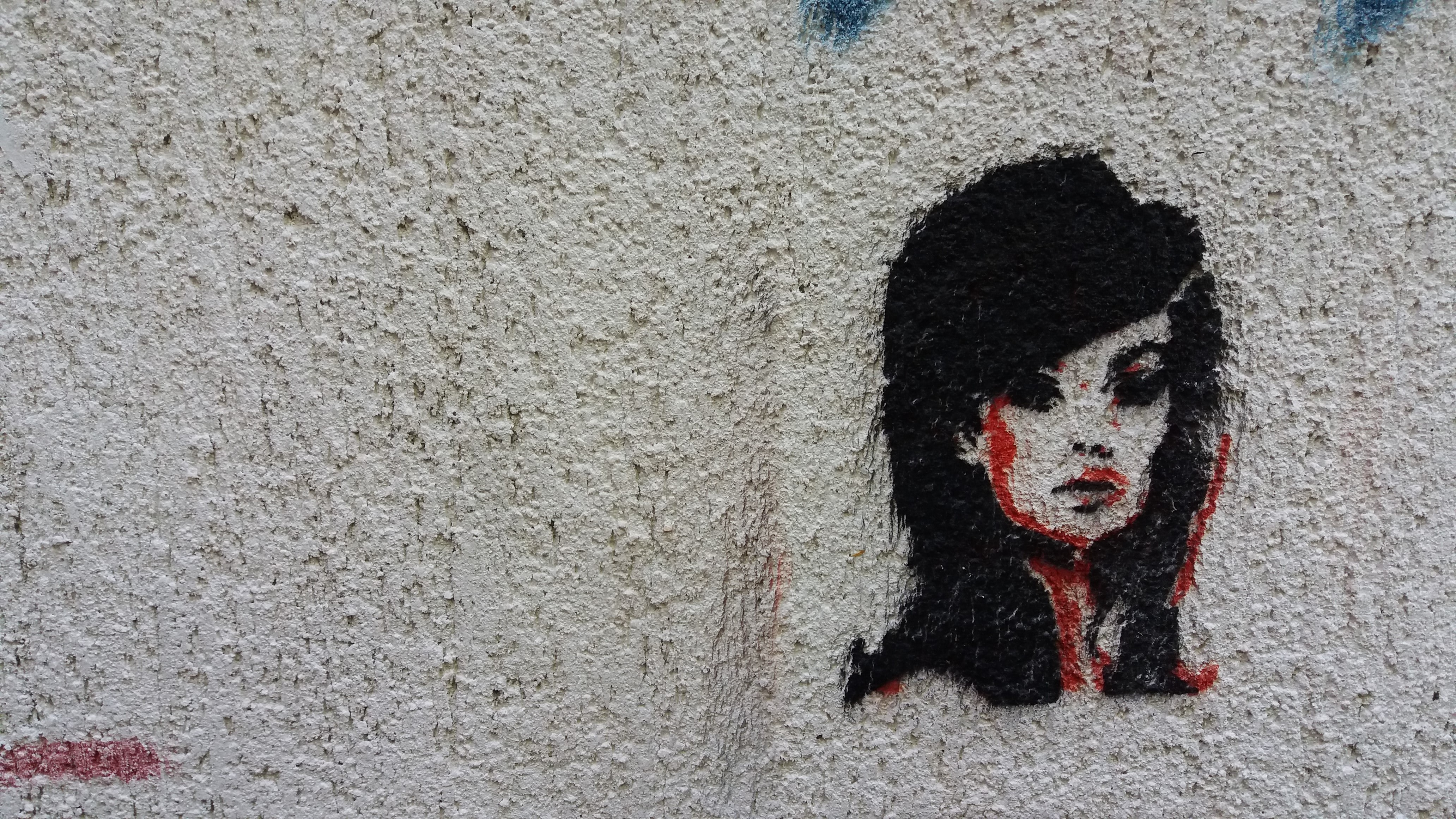 Black and red graffiti of woman's face with fashionable haircut on textured wall in Belgrade