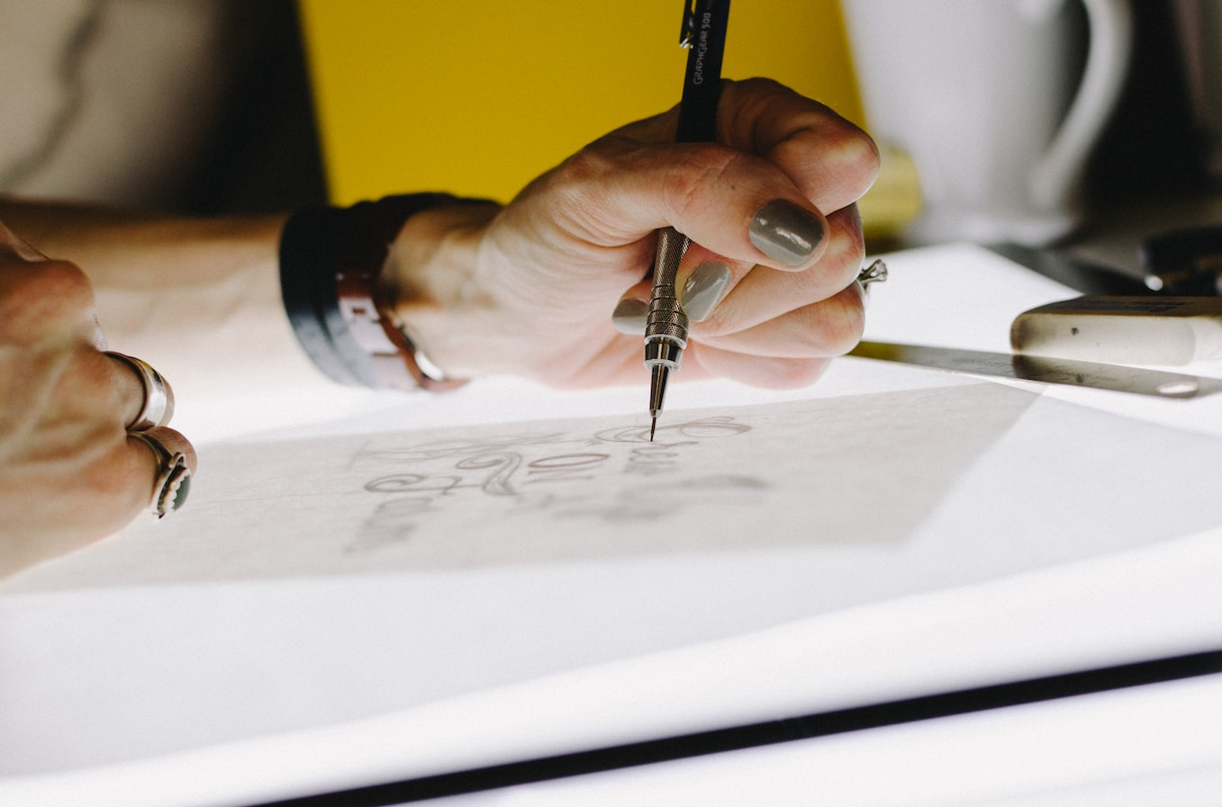 A woman drawing with a special typography pen