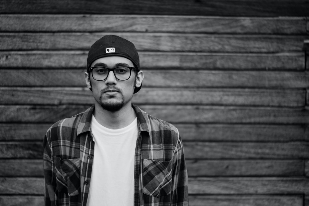 grayscale photo of man in plaid shirt and cap standing in front of wooden panel