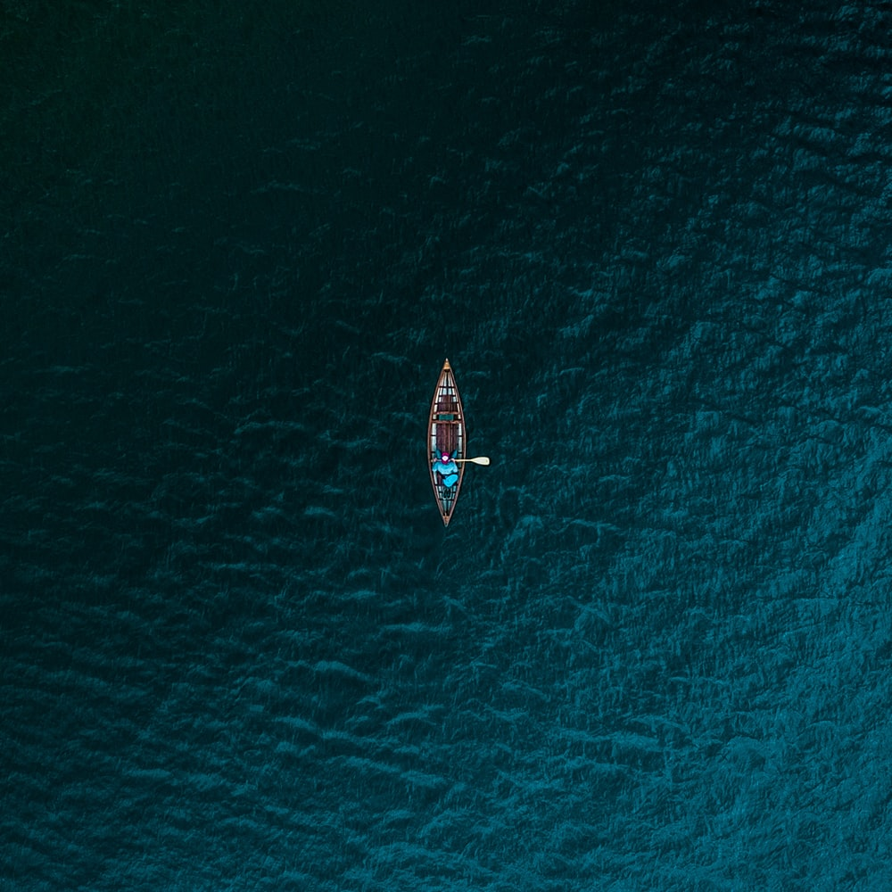 aerial photography of person riding boat on body of water