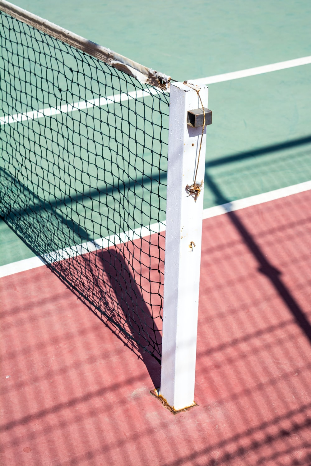 A focused shot of a post on one side of a tennis net.